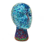 A foam mannequin head densely covered in light blue sequins and dark blue beads. There are scatterings of white and red beads across the face and neck.