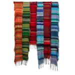 A series of long, rectangular weavings hanging in a row. The weavings are monochromatic in shades of orange, blue, green, and red, the shades change every few rows to look like stripes. There is a loose fringe on the end and left side of each weaving.