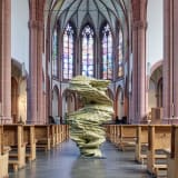 An image containing a sculpture by Tony Cragg, installed inside of a church.