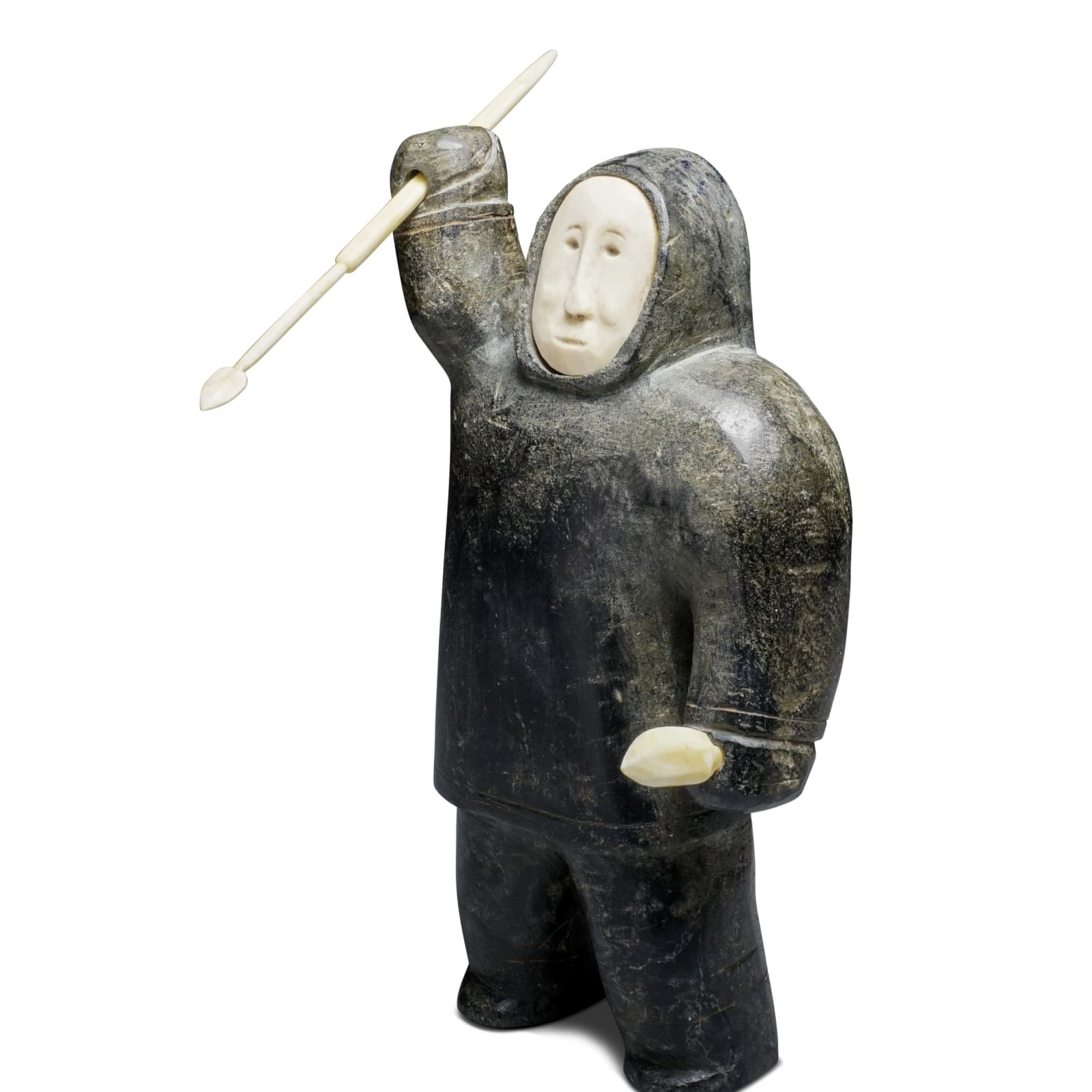LOT 22  UNIDENTIFIED ARTIST, INUKJUAK (PORT HARRISON) or PUVIRNITUQ (POVUNGNITUK) Standing Hunter Hurling Harpoon, c. 1950-3 stone, ivory, and graphite, 7 3/4 x 4 1/4 x 2 1/4 in (19.7 x 10.8 x 5.7 cm)  unsigned.  ESTIMATE: $800 — $1,200