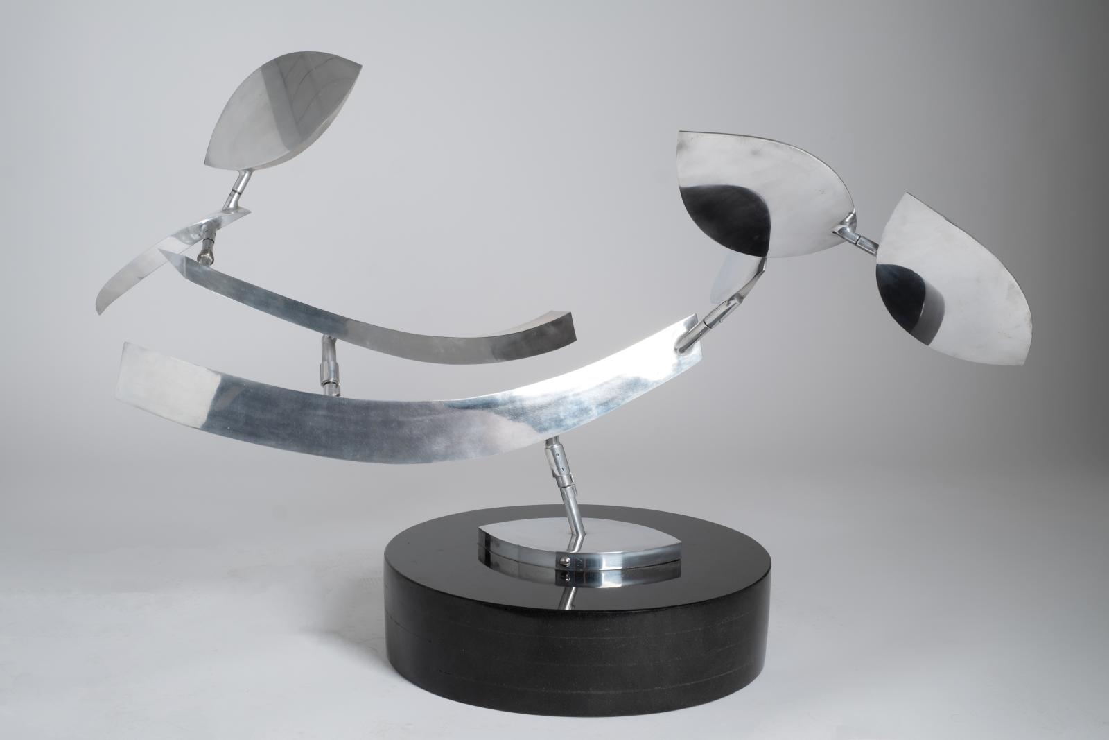 A polished aluminum sculpture consisting of two arms and four leaf shaped elements