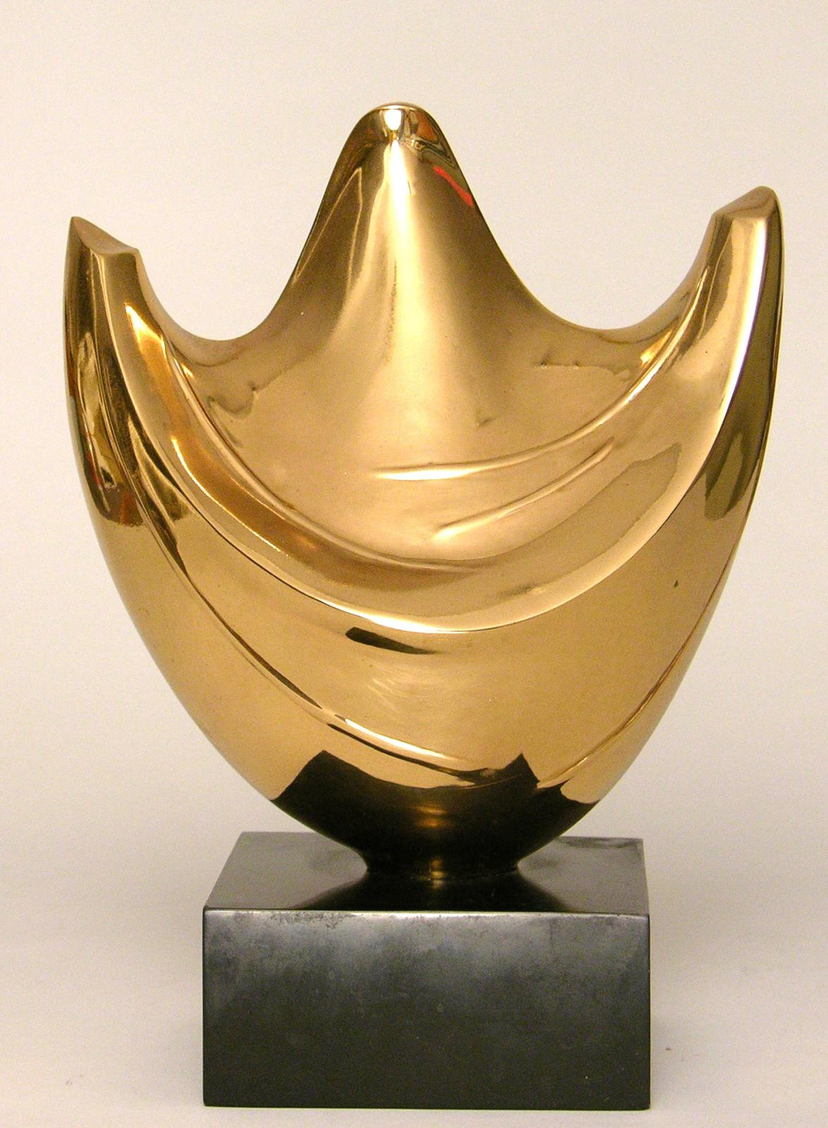 A polished bronze sculpture, an abstracted figure with arms raised