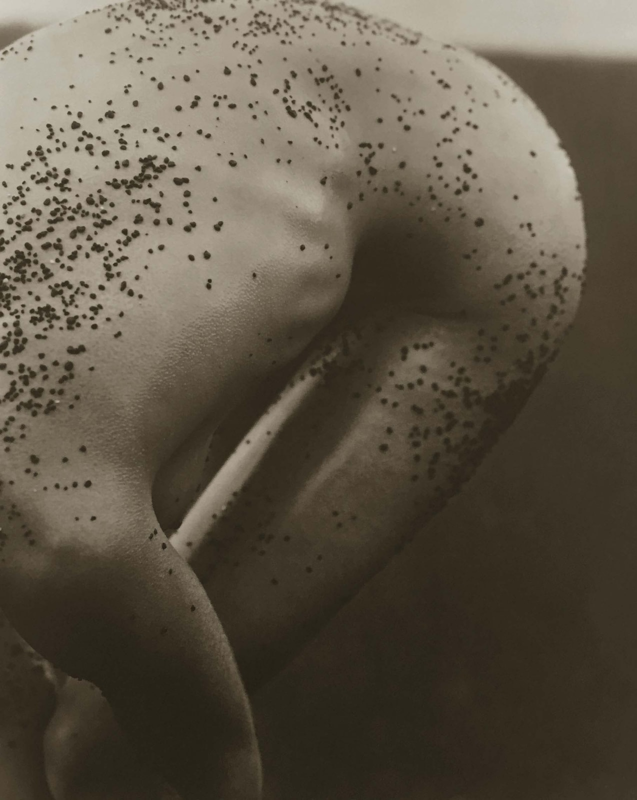 Herb RItts photograph of female torso with black sand, Hawaii
