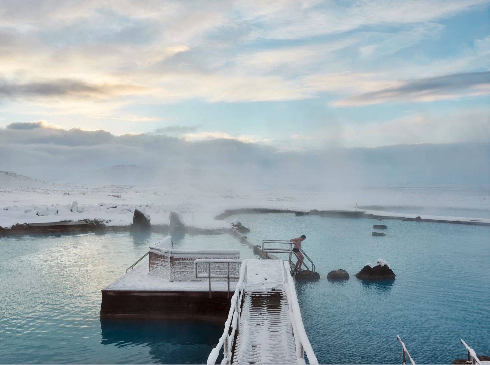 Lone figure stepping into hot pools in Iceland at Myvatn Nature Baths, by Massimo Vitali