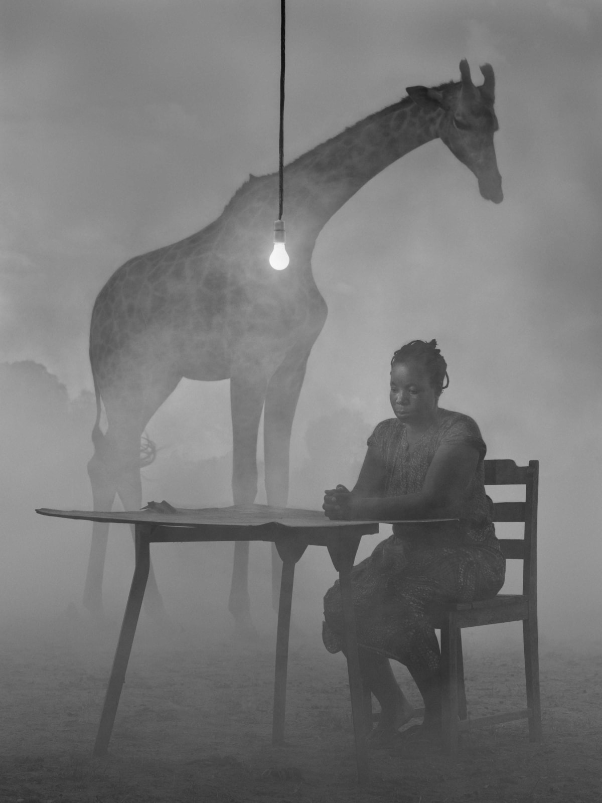 Kuda sitting at table with giraffe named Sky behind her, lightbulb hanging over table, Zimbabwe, from the Dawn May Break series by Nick Brandt