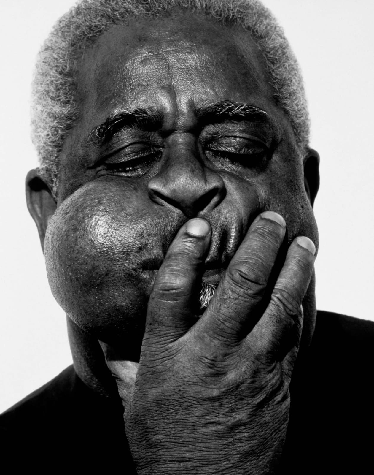 Herb Ritts photograph of Dizzy Gillespie with cheek inflated, hand on mouth, Paris