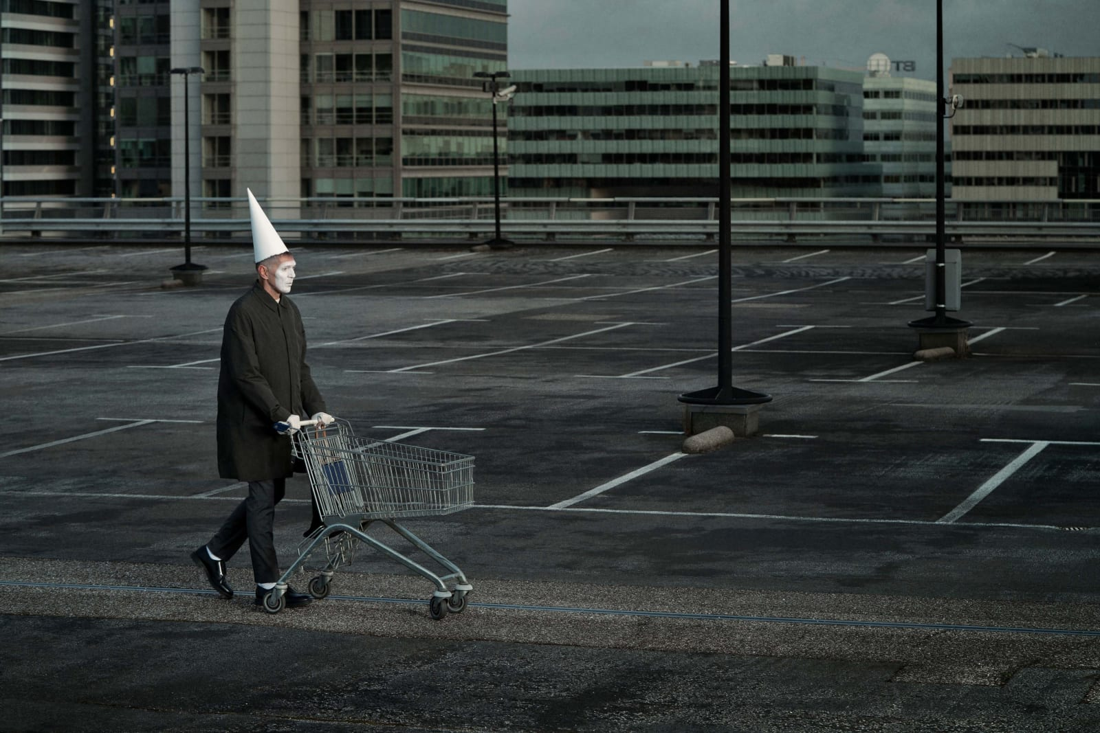 Erwin Olaf with face painted white in white dunce cap pushing an empty shopping cart through an empty parking lot, by Erwin Olaf