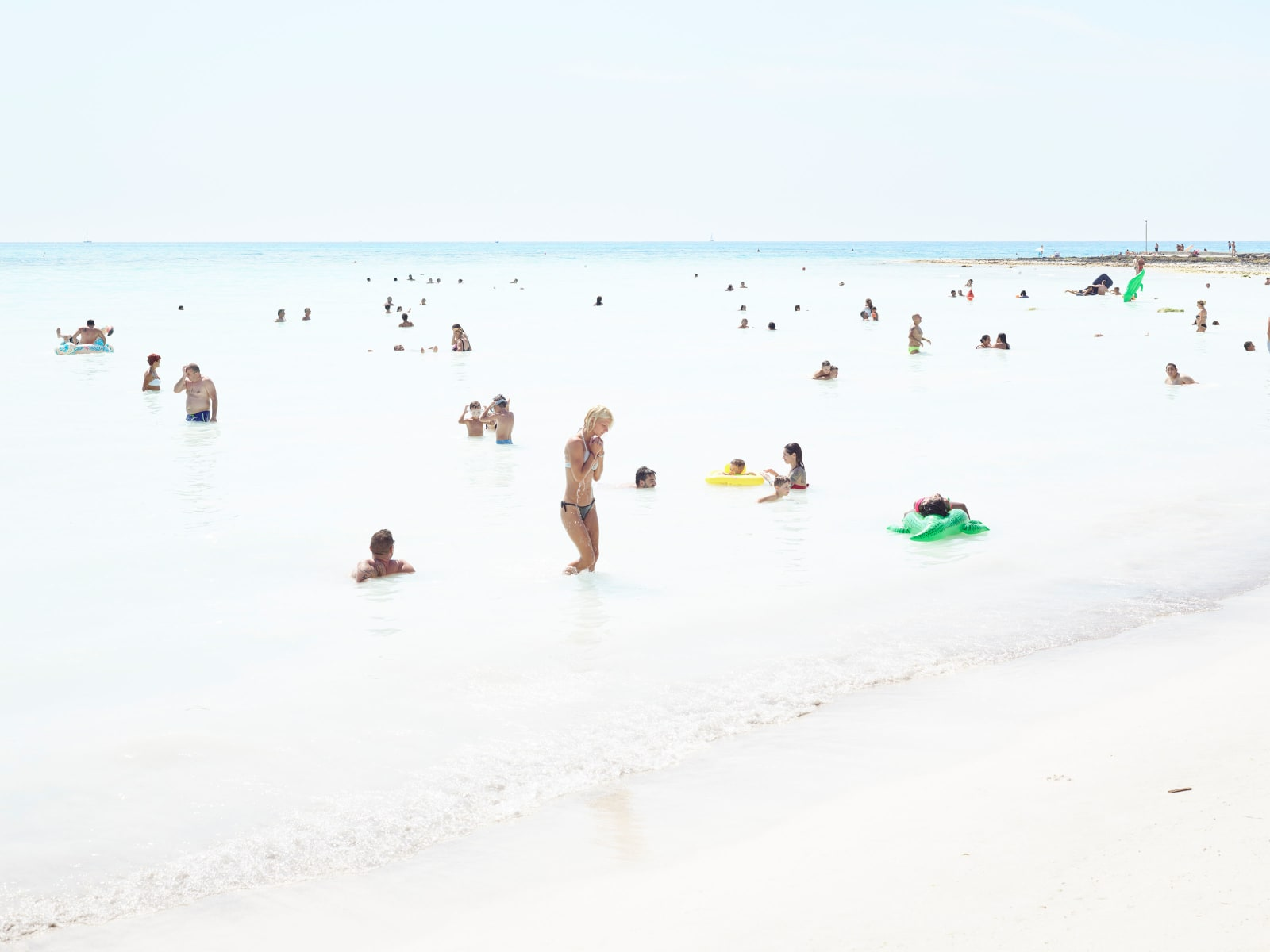 Blonde woman clasping hands in front of chest in ocean with other swimmers, by Massimo VItali
