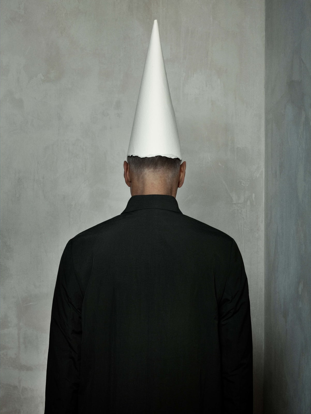 Erwin Olaf self portrait from behind, artist wearing dunce cap and looking at wall, by Erwin Olaf