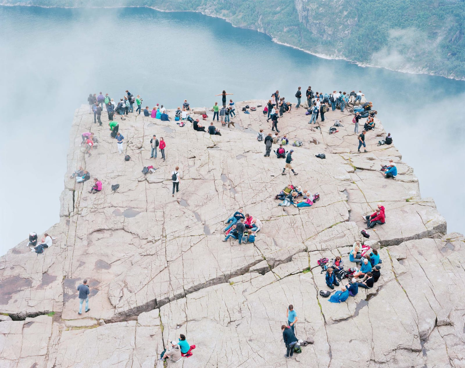 Groups of hikers on very tall cliff at Pulpit Rock above steaming water, Preikestolen Norway, by Massimo Vitali