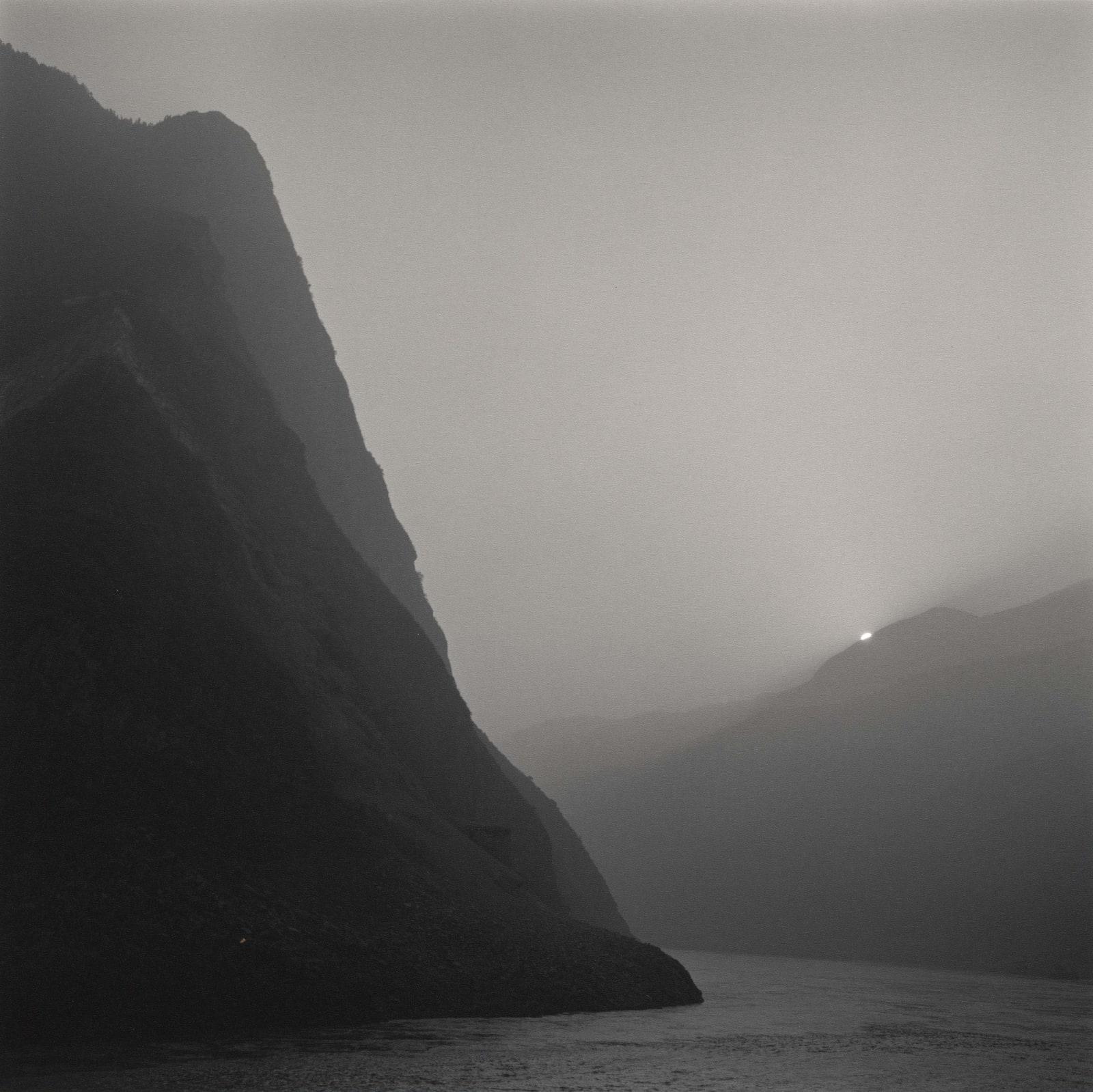 Lynn Davis photograph of Three Gorges, Yangtze River, China, with sun setting along mountain silhouette