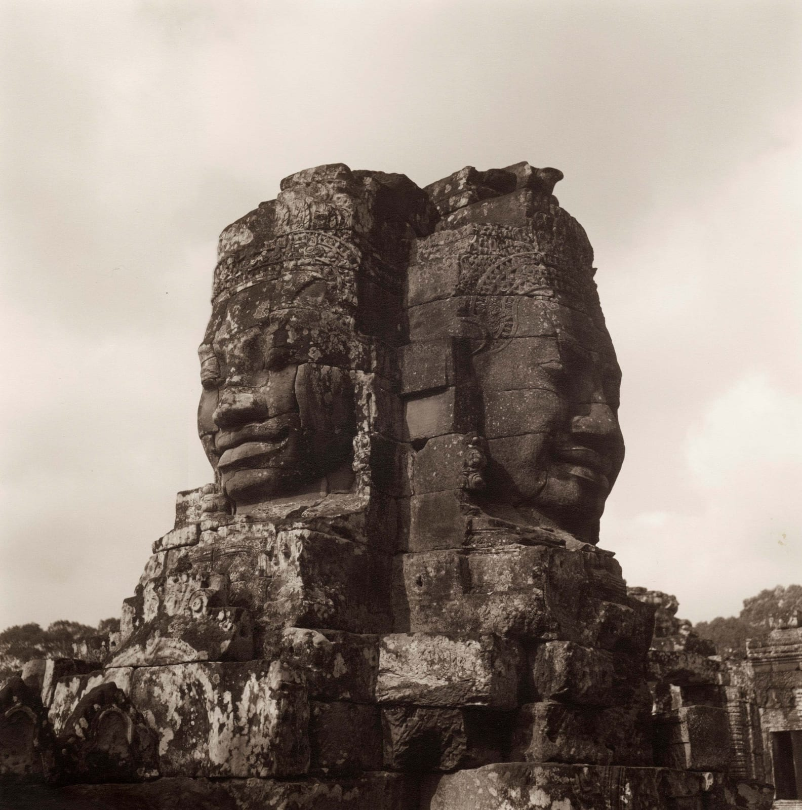 Lynn Davis photograph of two heads carved from mountain at the Bayon, Angkor Wat, Cambodia
