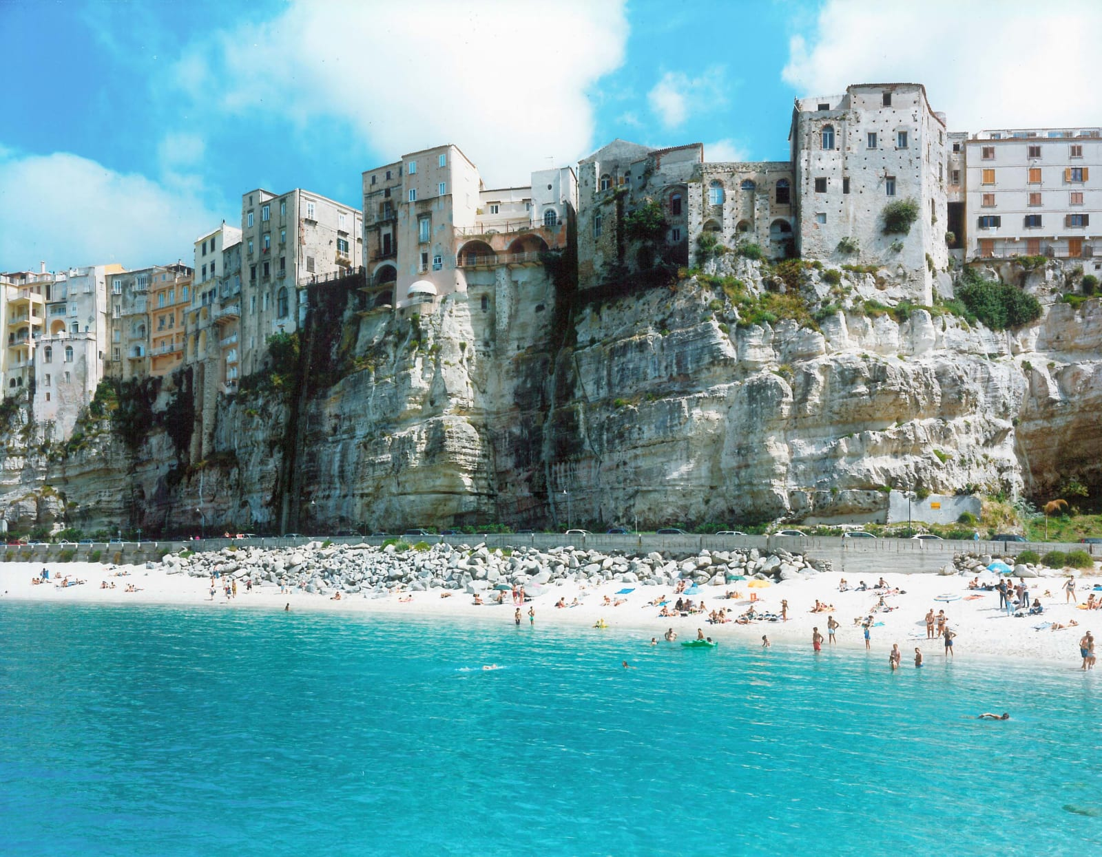 Aquamarine sea with beachgoers, below old buildings built on cliffs, by Massimo Vitali