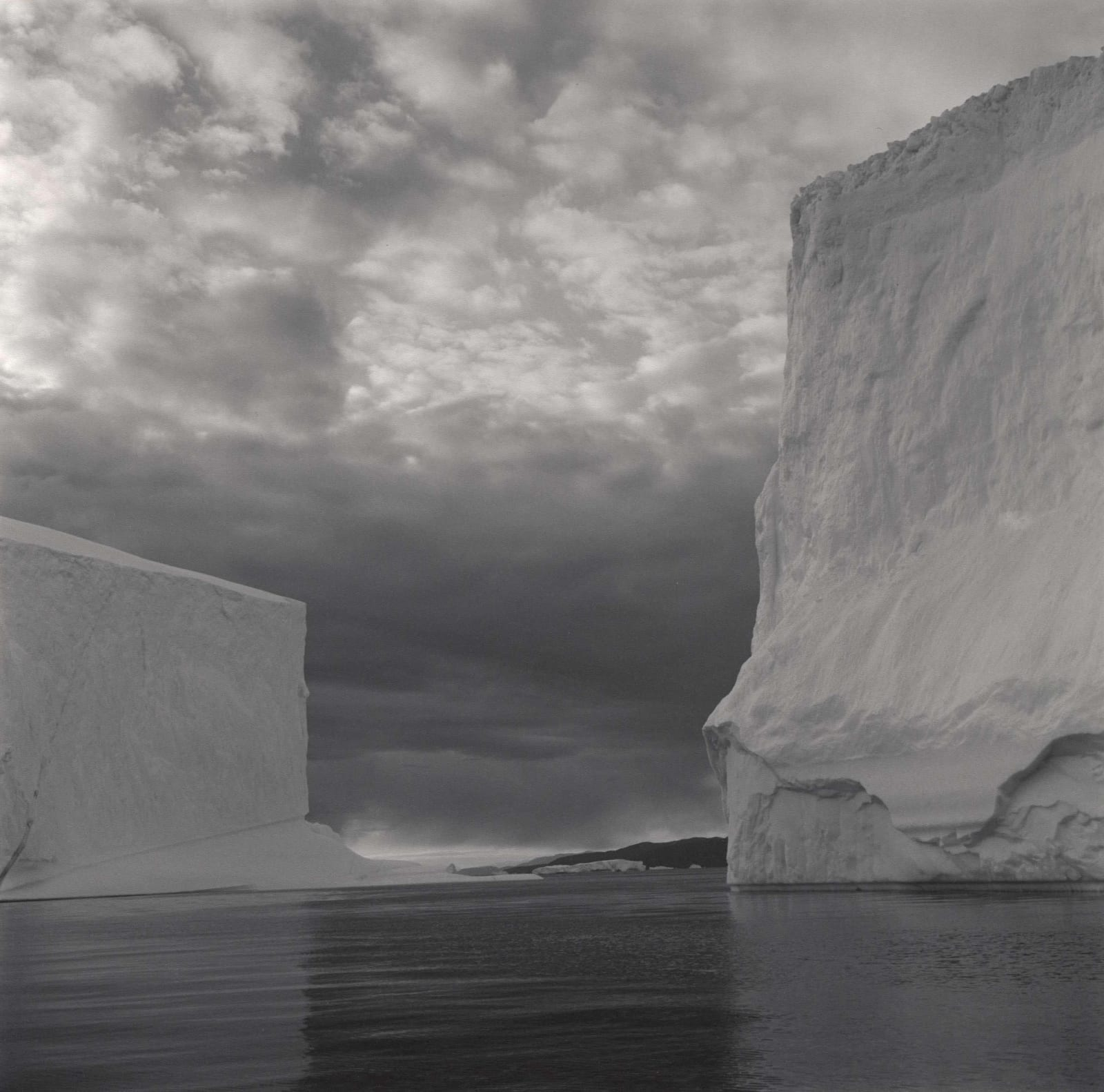Lynn Davis photograph of two geometric icebergs in Disko Bay, Greenland, with cloudy sky and inky water