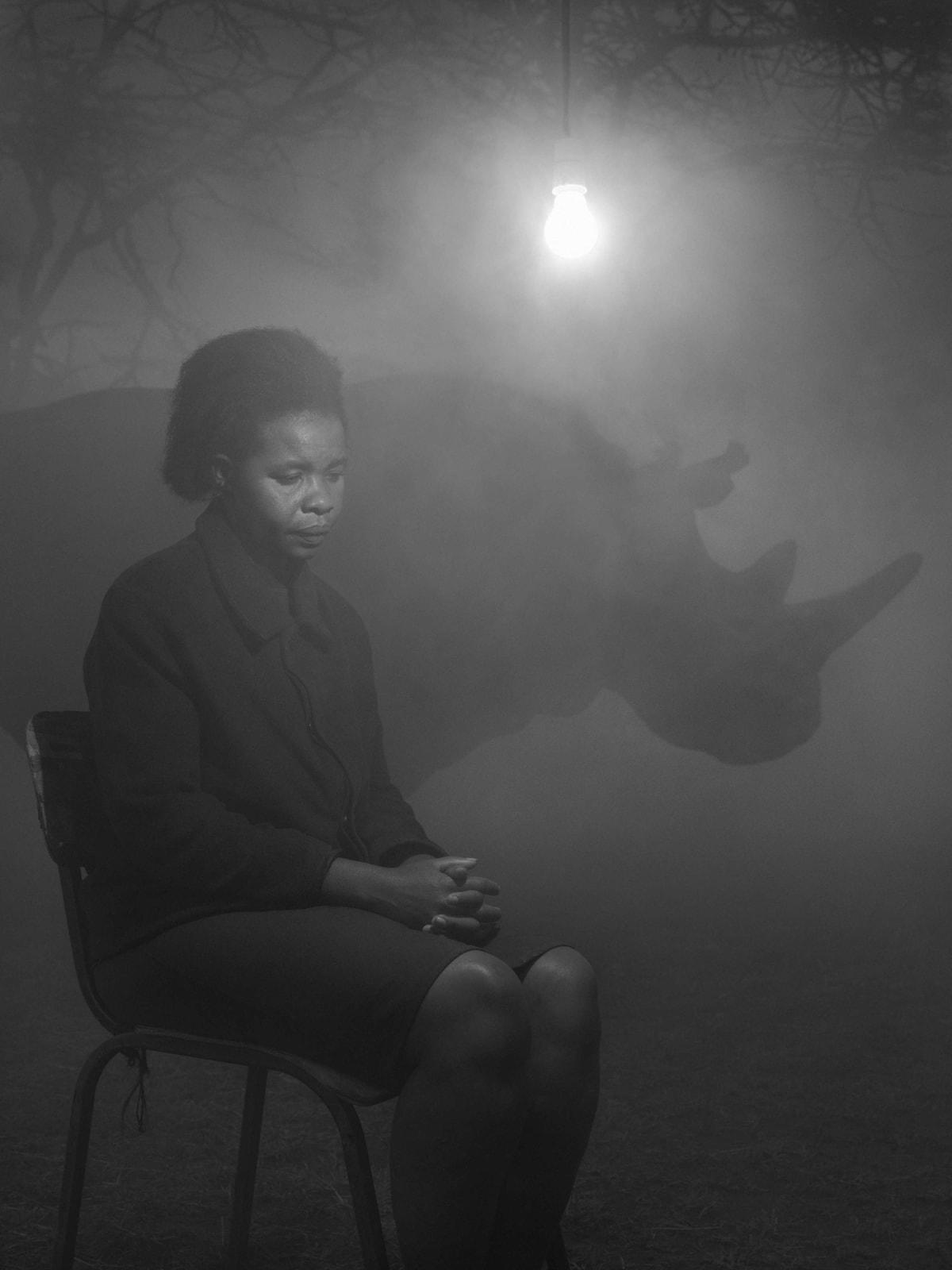 Teresa and a rhino named Najin in fog with lightbulb, Kenya, from the Day May Break series by Nick Brandt