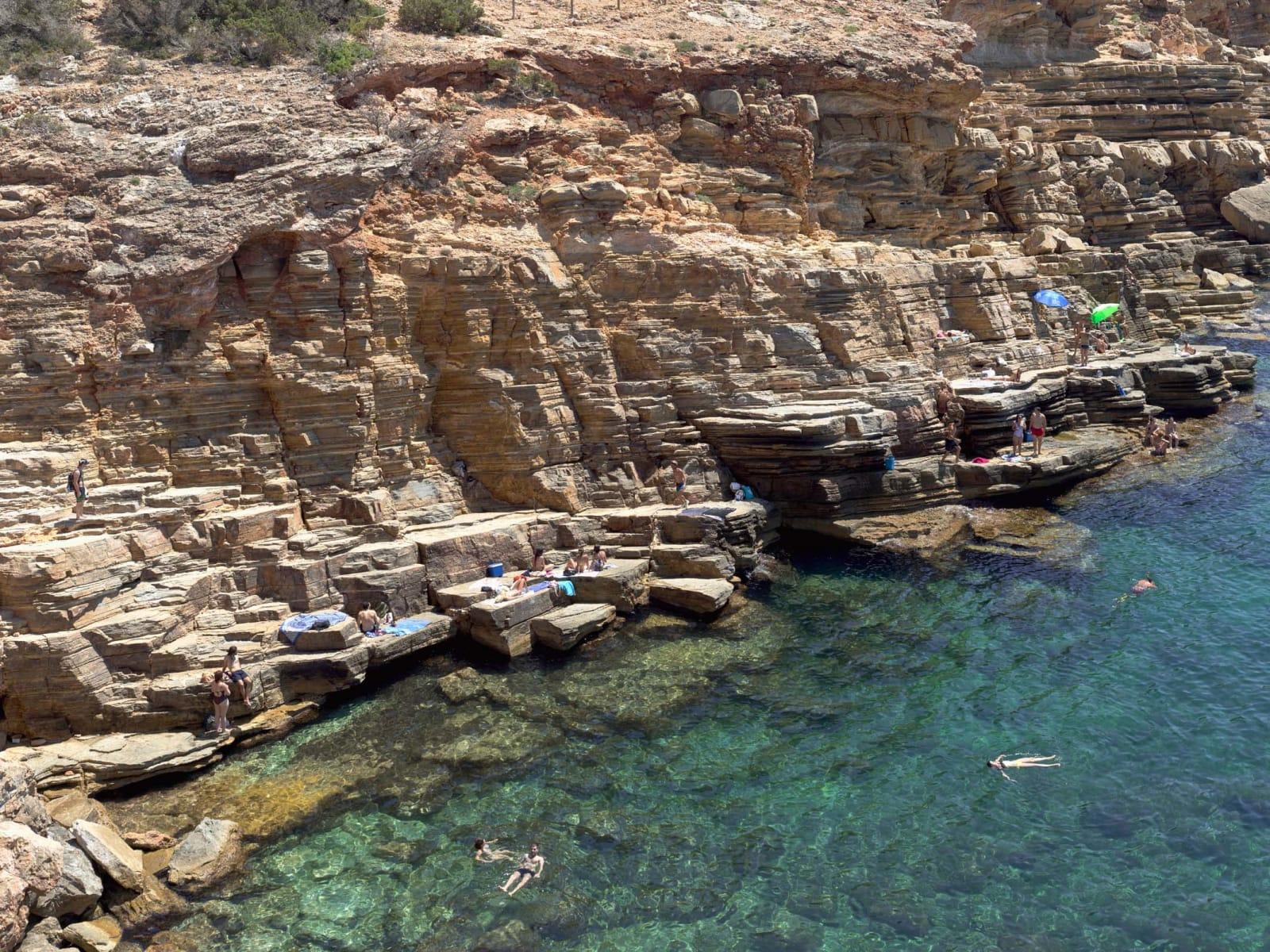 Beachgoers floating in blue water at Cala Llosa South, Ibiza, by Massimo Vitali