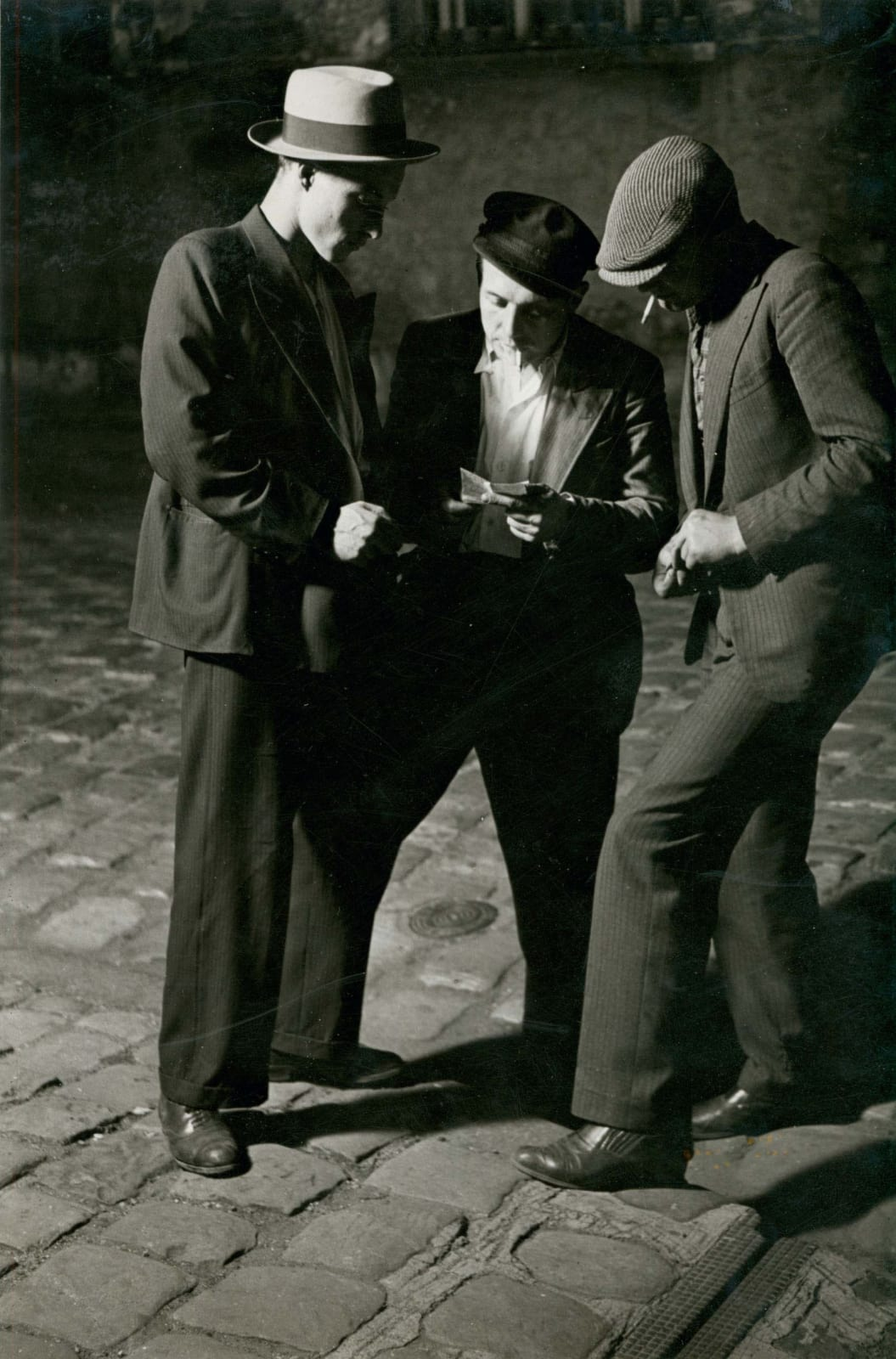 Brassai photograph of three young men in Paris street at night