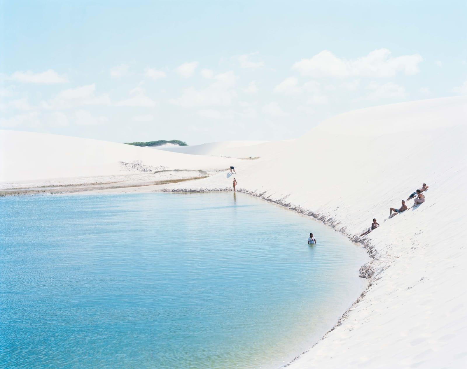 Sunbathers on white sand dunes relaxing next to blue water, at Lençóis Maranhenses National Park, Brazil, by Massimo Vitali