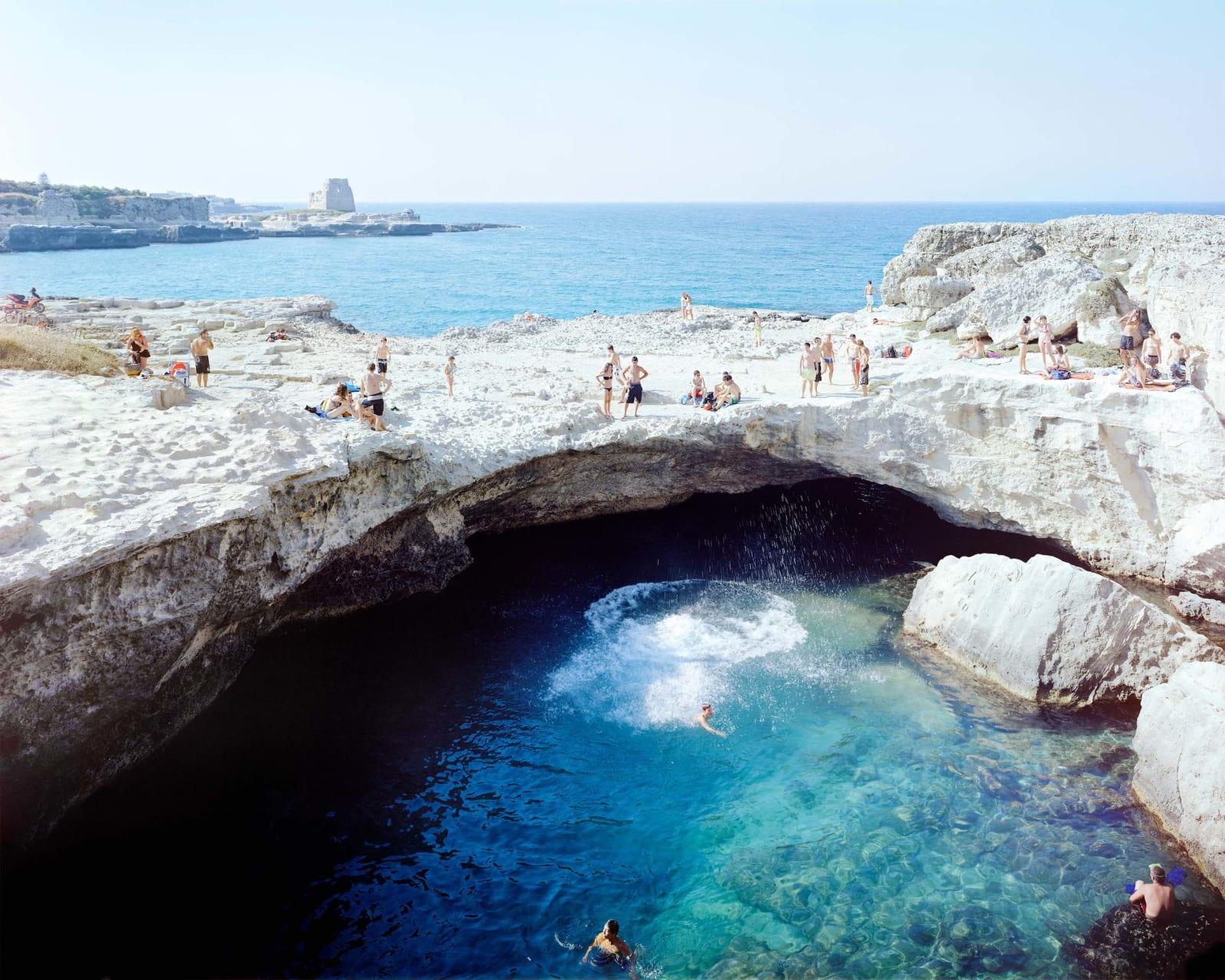 Beachgoers sunbathing at grotto Poesia Tuffo, Italy by Massimo Vitali