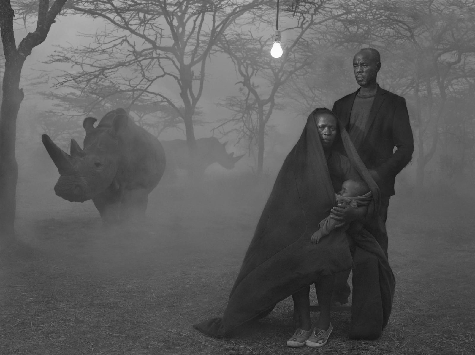 Alice, Stanley, and baby with rhino Najin in foggy background, Kenya, from the Dawn May Break series by Nick Brandt