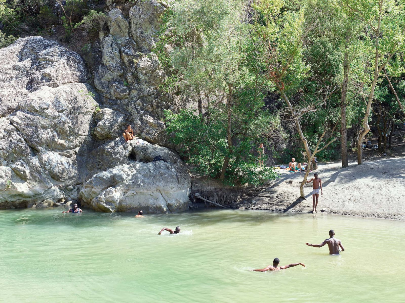 Three swimmers in green-tinted water with a girl sitting on a boulder, by Massimo Vitali