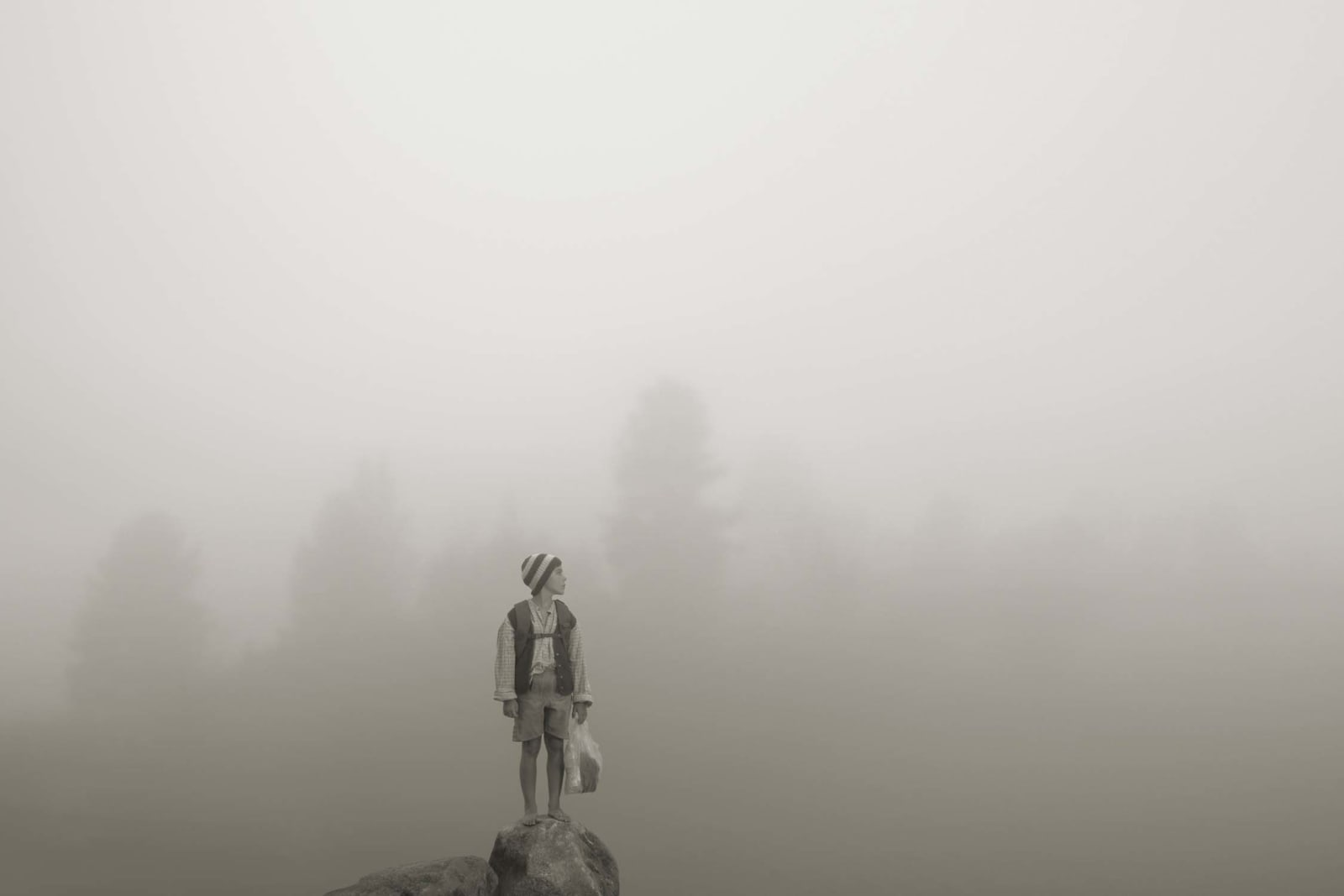 Young boy on mountain top in front of misty landscape, by Erwin Olaf