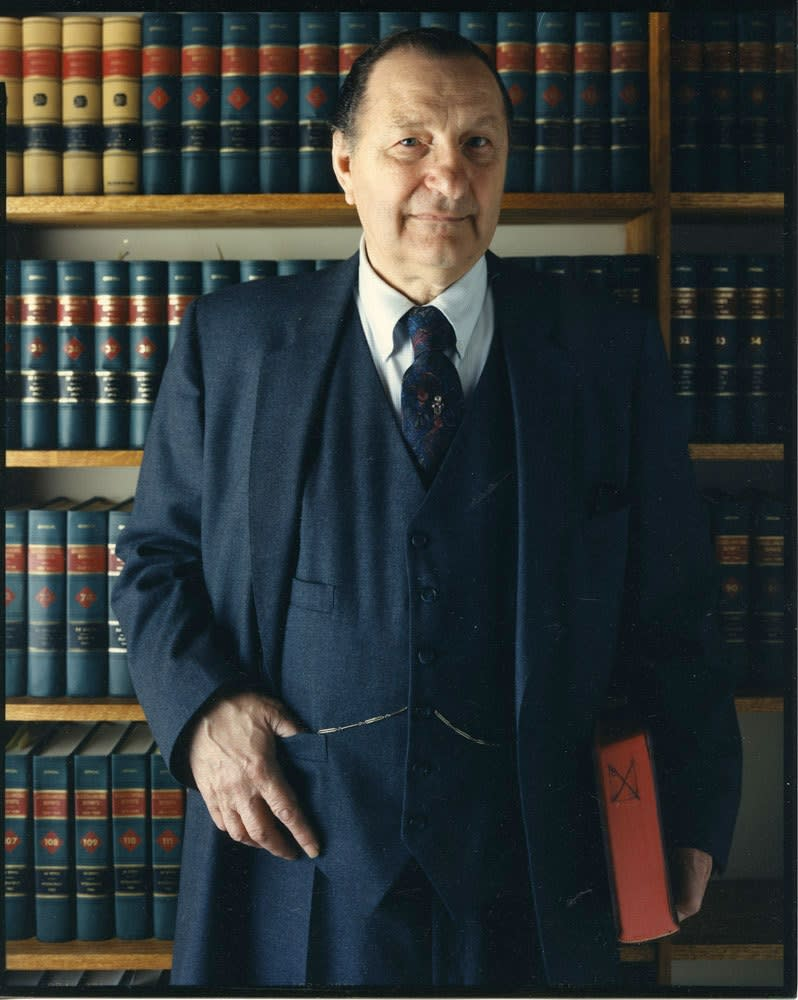 Bruce Wrighton, Man in 3-piece suit, holding book, in front of library shelves