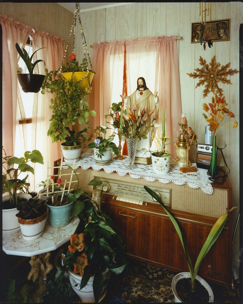 Bruce Wrighton Jesus statue on top of stereo console, plants on console, table, and floor, in front of corner windows Tirage C-print d'époque 20 x 25 cm Dim. papier: 20 x 25 cm
