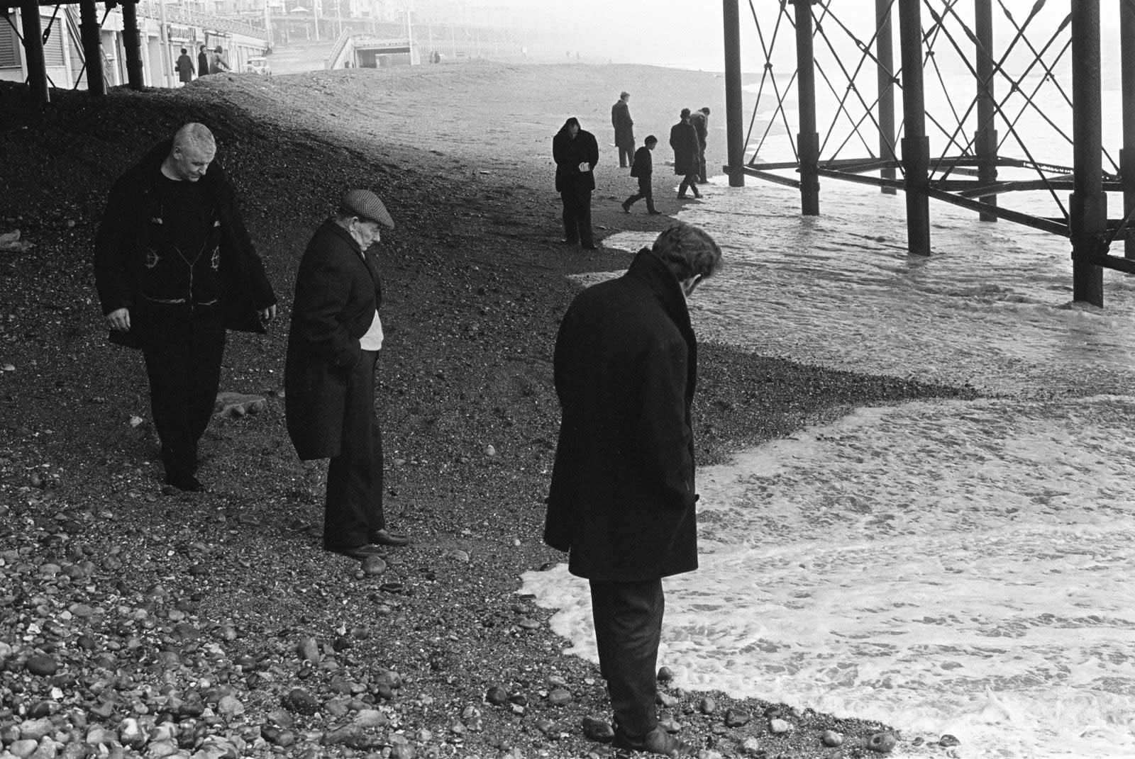 Homer Sykes, Blacksanding, sunday morning, under Brighton Pier looking for coins that are washed up, Brighton, Sussex, 1970