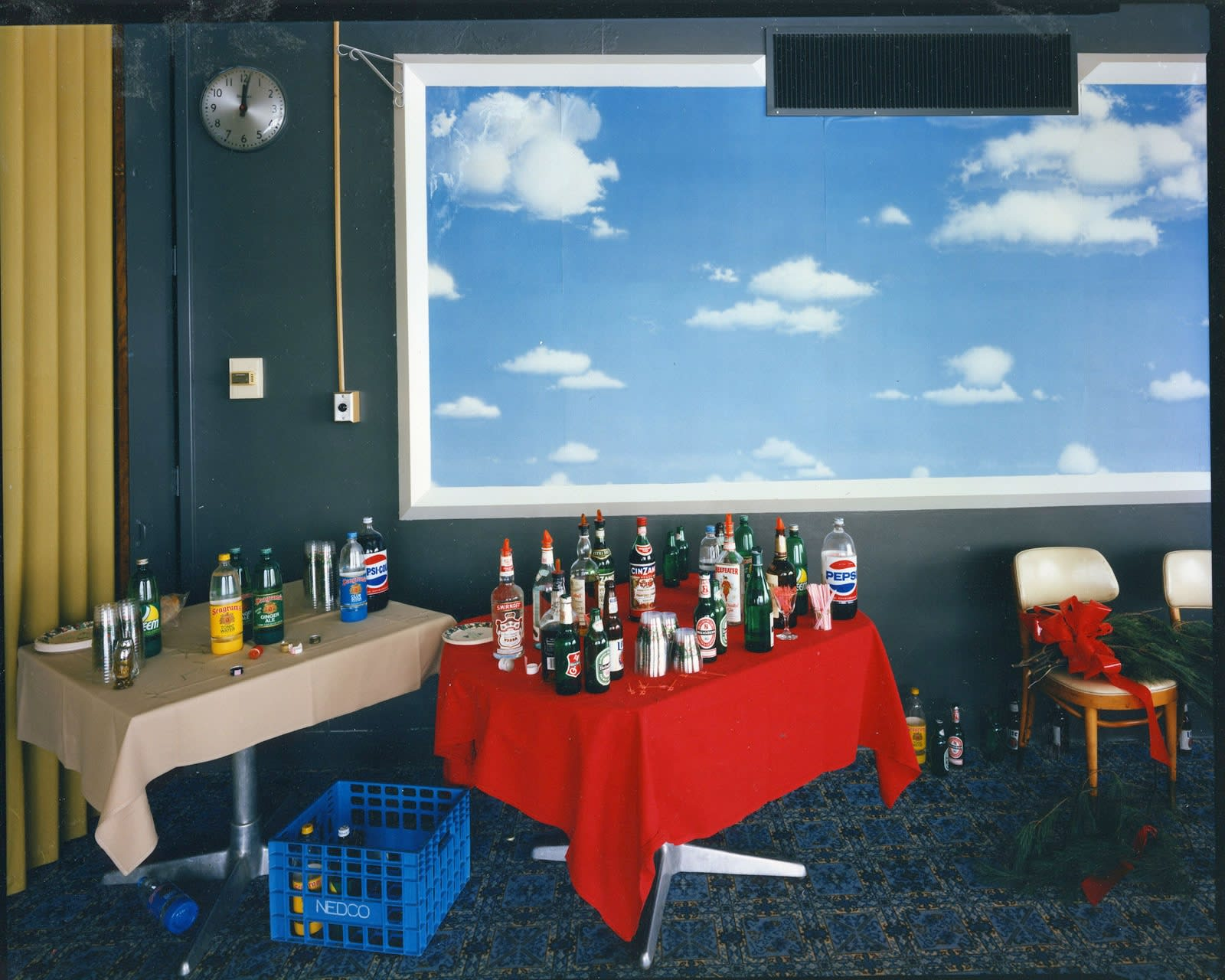 Bruce Wrighton, Framed clouds with blue sky, over 2 tables with soda/liquor bottles (red and tan tablecloths)