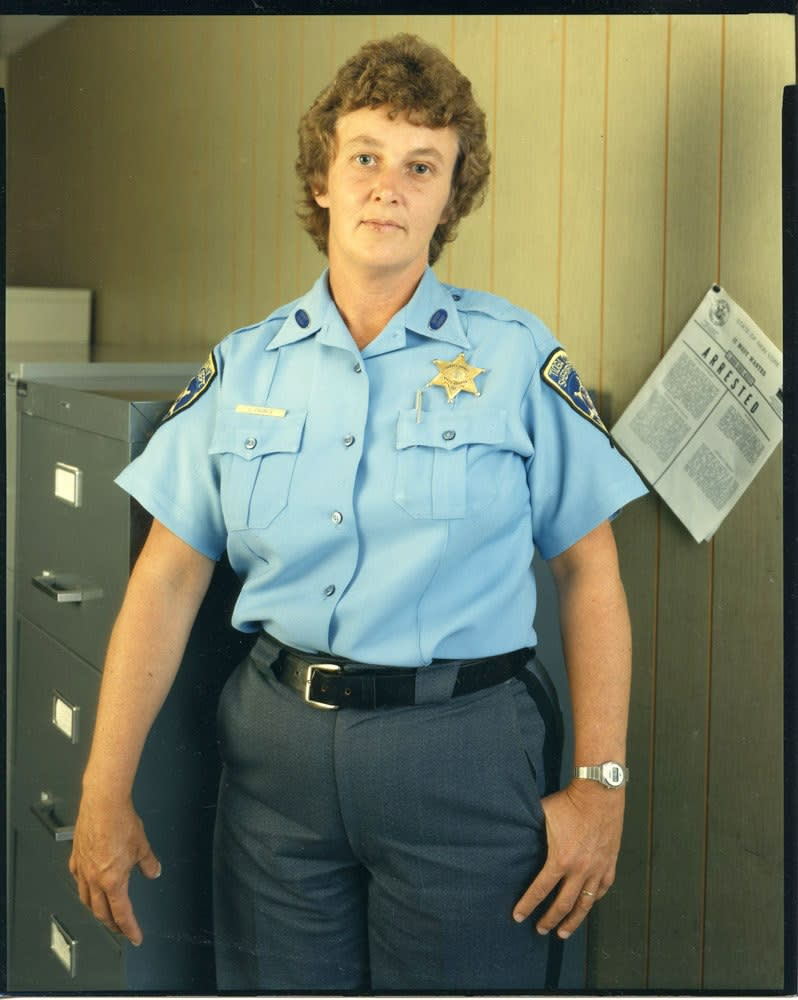 Bruce Wrighton Woman in blue Tioga County Sheriff uniform, with file cabinet on left and ARRESTED noticed on right Tirage C-print d'époque 20 x 25 cm Dim. papier: 20 x 25 cm