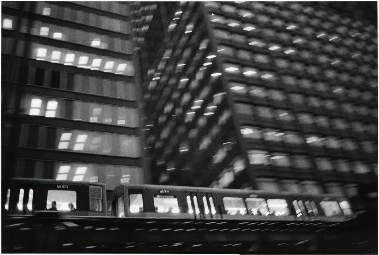 Sid Kaplan, Blurry view of train and building, windows at night, Chicago, 1978