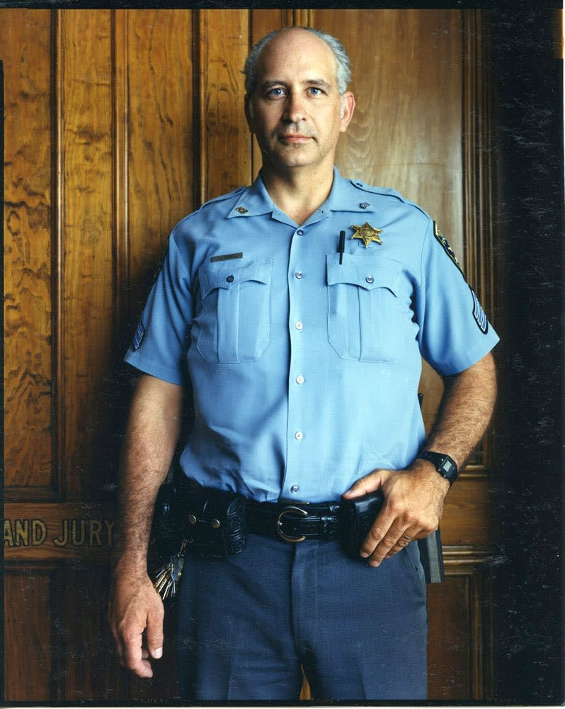 Bruce Wrighton, Court officer in blue uniform, in front of Grand Jury door