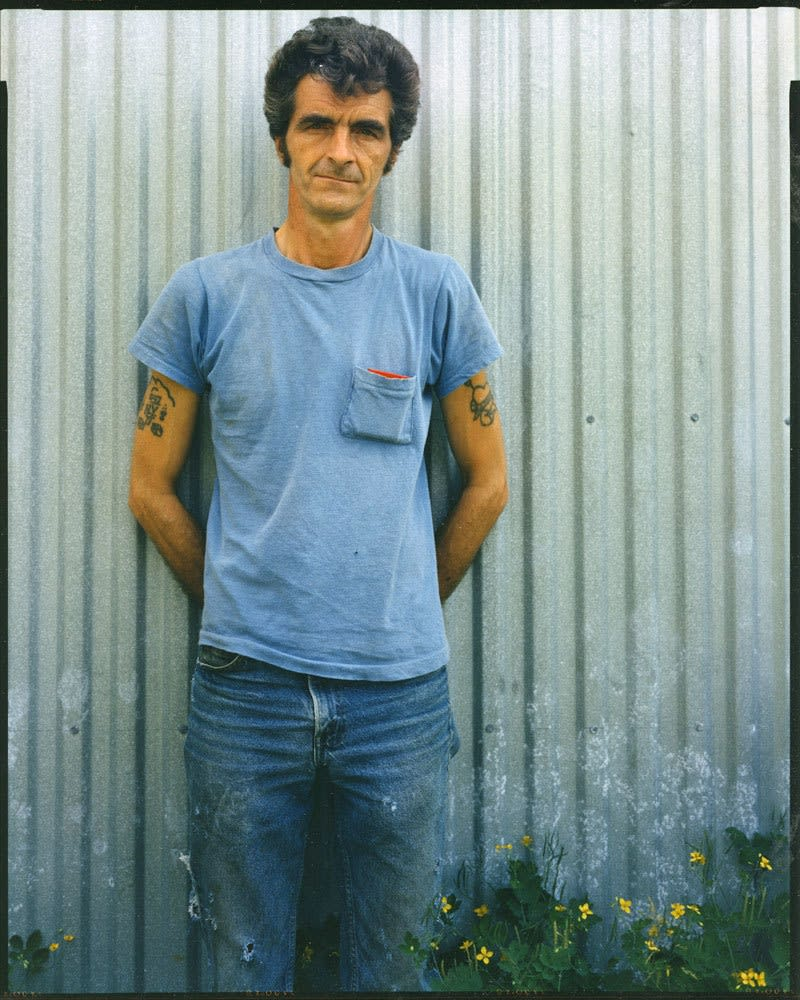 Bruce Wrighton Man with tattoed arms, in blue t-shirt, in front of green corrugated fence, yellow flowers at bottom Tirage C-print d'époque 20 x 25 cm Dim. papier: 20 x 25 cm