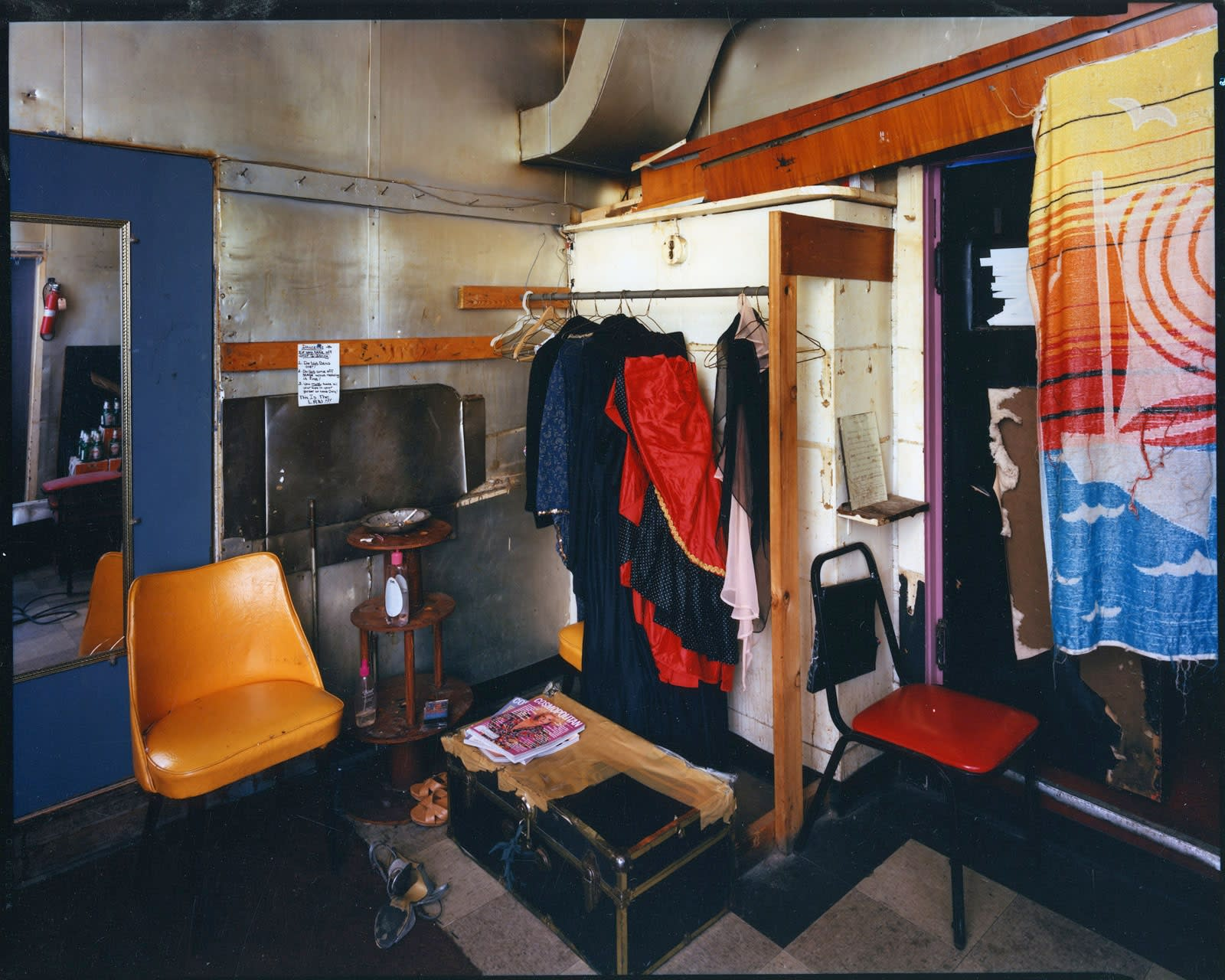 Bruce Wrighton Gold chair on left, in front of mirror, trunk on floor, clothes hanging from rod Tirage C-print d'époque 20 x 25 cm Dim. papier: 20 x 25 cm