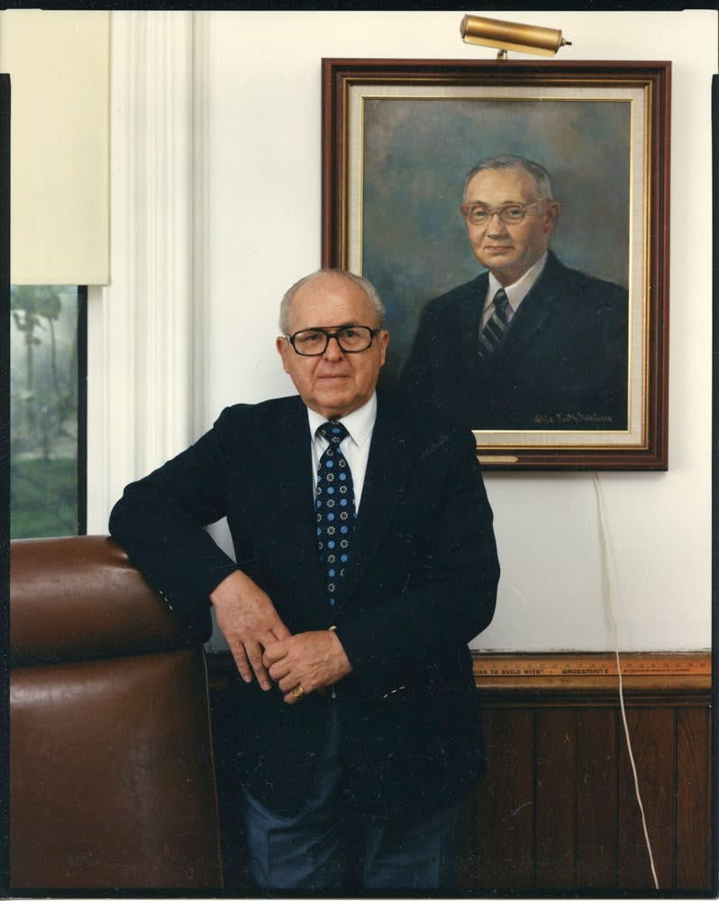 Bruce Wrighton, Man in dark suit in front of framed portrait on wall