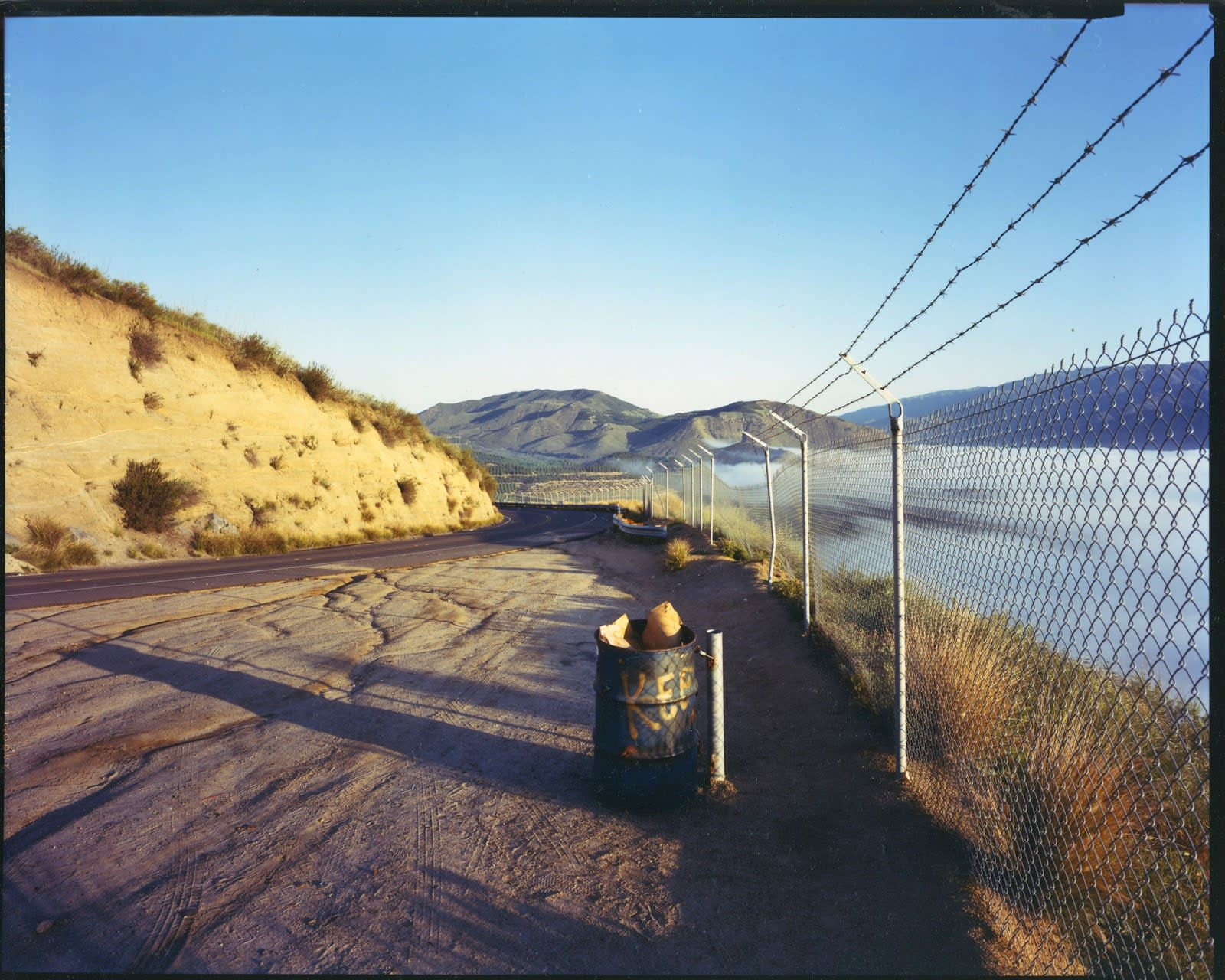Bruce Wrighton, Hills in distance, eastern berm on left, chian-link fence on right, trash can center
