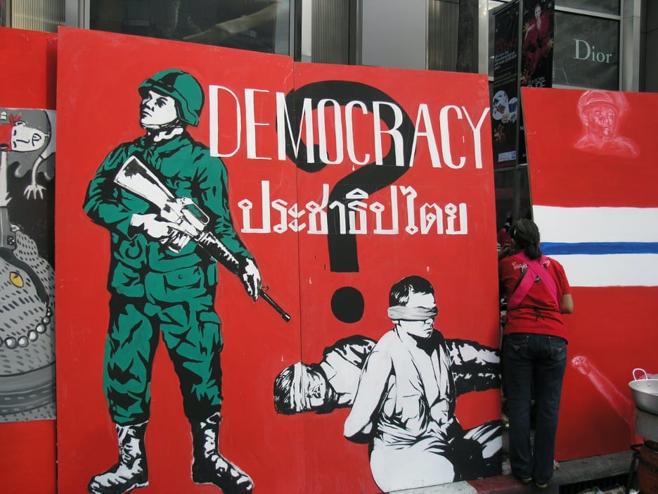 Sign at a Red Shirt protest reading: 'This, or Democracy?' The words spilling from the gun of the tank read: 'Blood of the people'