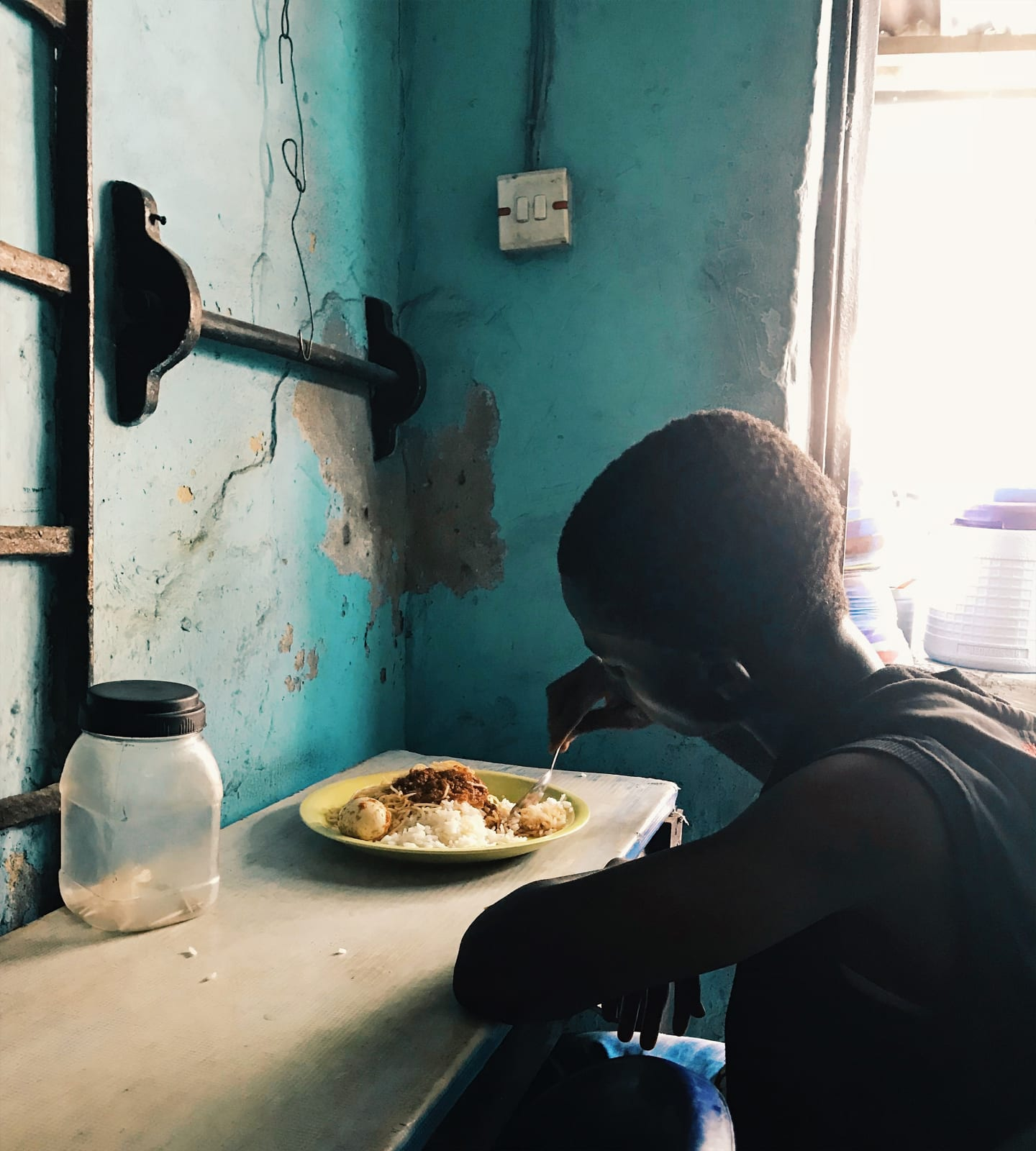 Arinzechukwu Patrick A boy enjoys his meal in a small restaurant 25.2 x 28 cm 19 x 21 cm Digital print