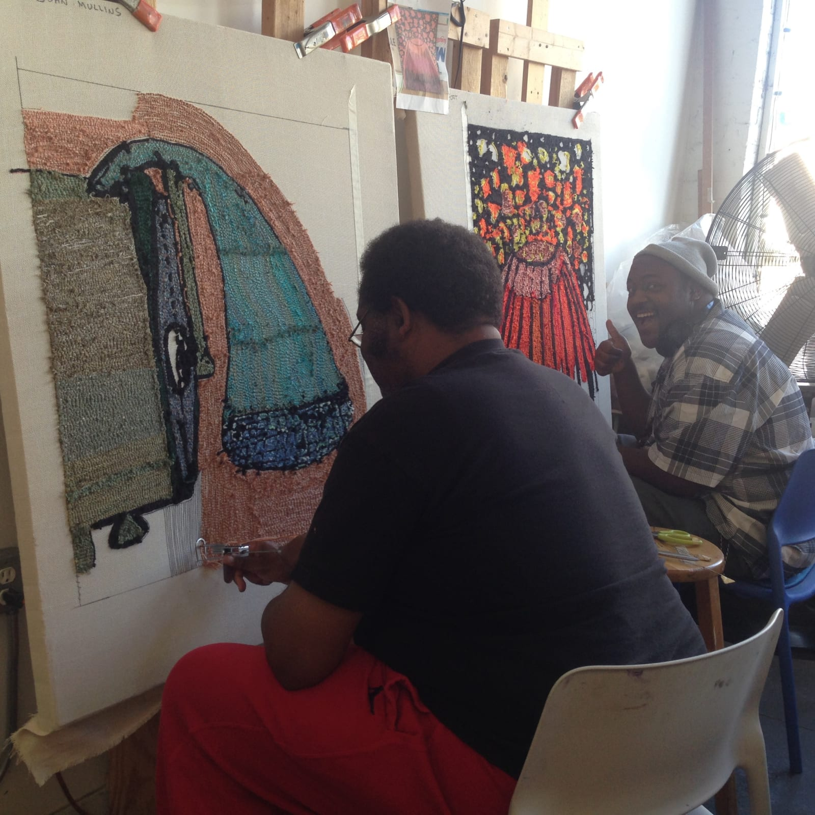 Artists Larry Randolph (left) and Ray Vickers, working on rugs designed by John Mullins (alum) and D'Lisa Fort, respectively.