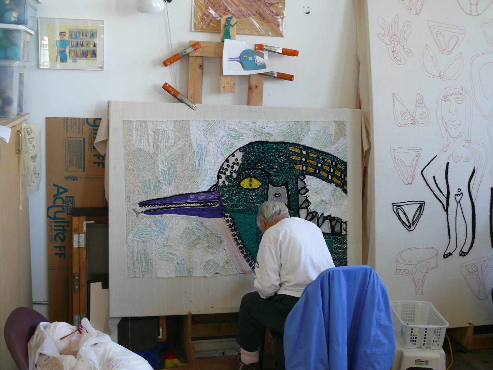 A Creative Growth artist works on a rug designed by Valerie Tribble, a rug designed by Juan Aguilera is visible at the right.