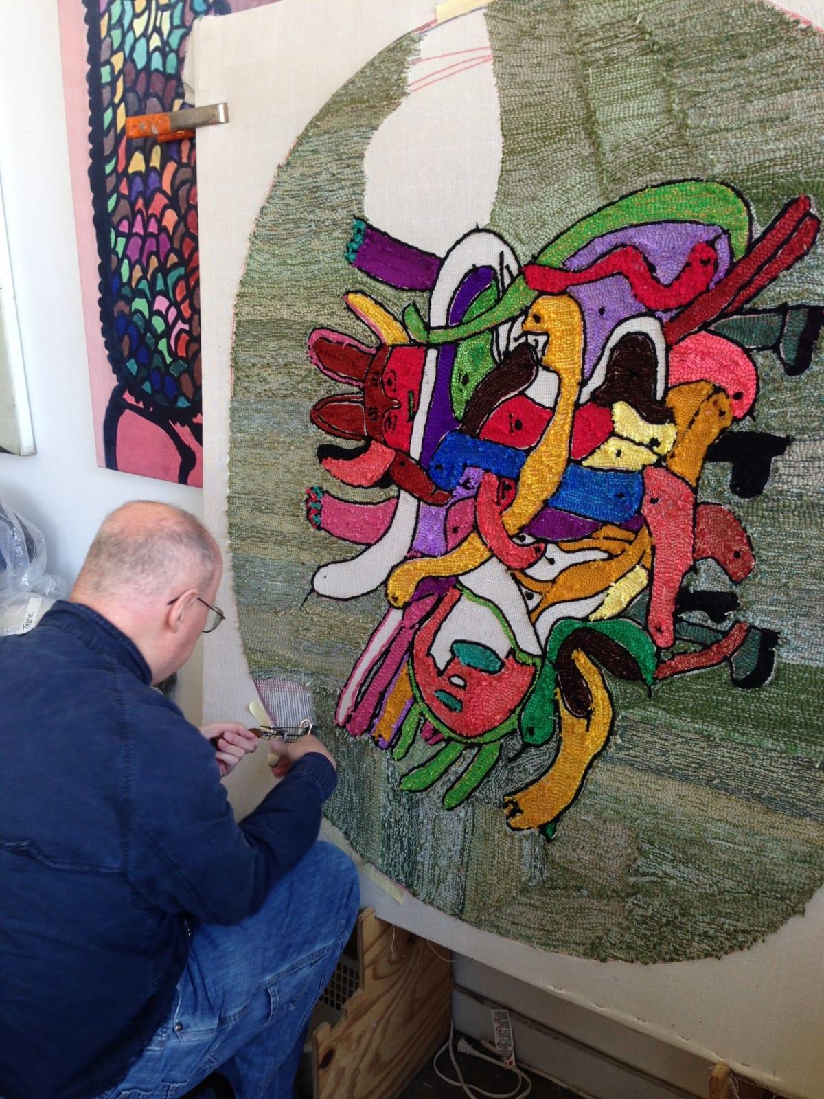 Artist William Tyler works on a rug designed by Creative Growth alum Merritt Wallace.