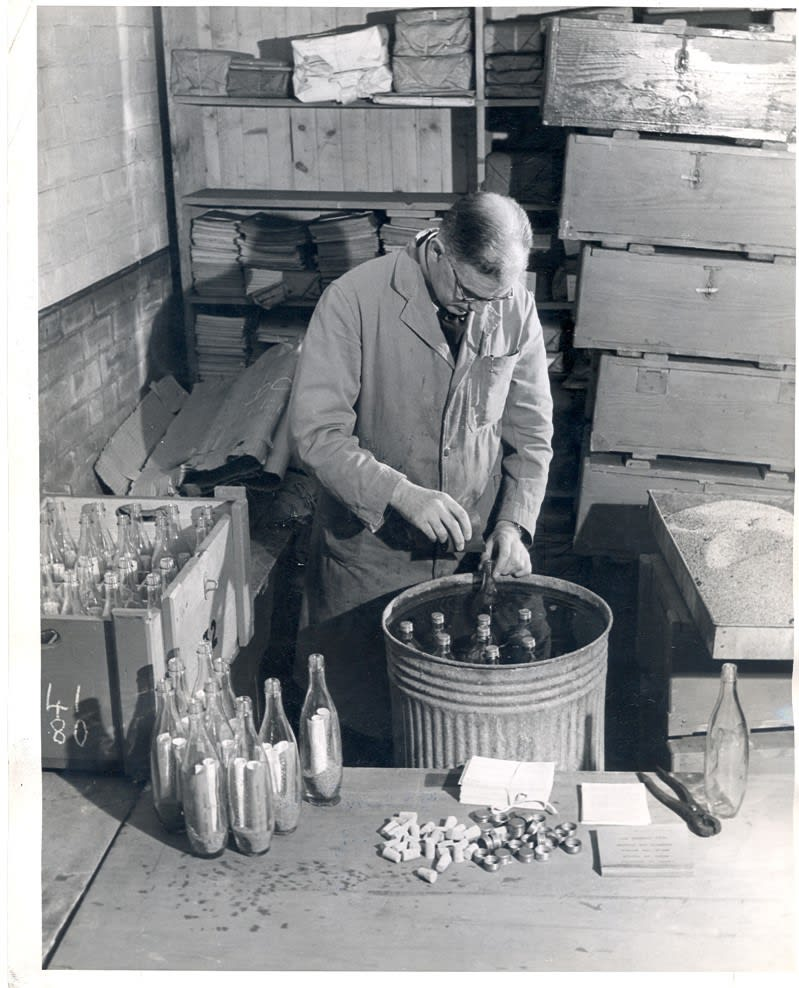 Rognvald Livingstone preparing drift bottles ahead of their deployment. He ballasts each glass bottle with sand and makes sure to include an instruction card for potential finders. (C) Marine Scotland and Crown Copyright