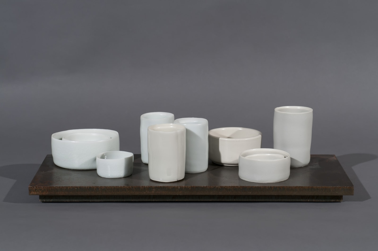 Edmund DE WAAL (b.1964) 9 circles II, 2011 Edition 2 of 10 A series of corten steel slabs each with 9 thrown porcelain vessels in celadon, grey and white glazes 5 7/8 x 13 ¾ x ½ inches / 15 x 35 x 2 cm
