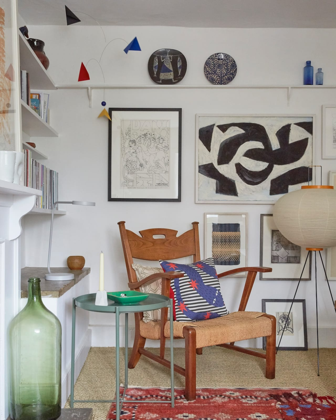 The shelf at picture-rail height was a relic of the former tenant, which Tobias kept as a display. Here a Noguchi lamp sits with an MMF rug and Paolo Buffa chair in the sitting room.