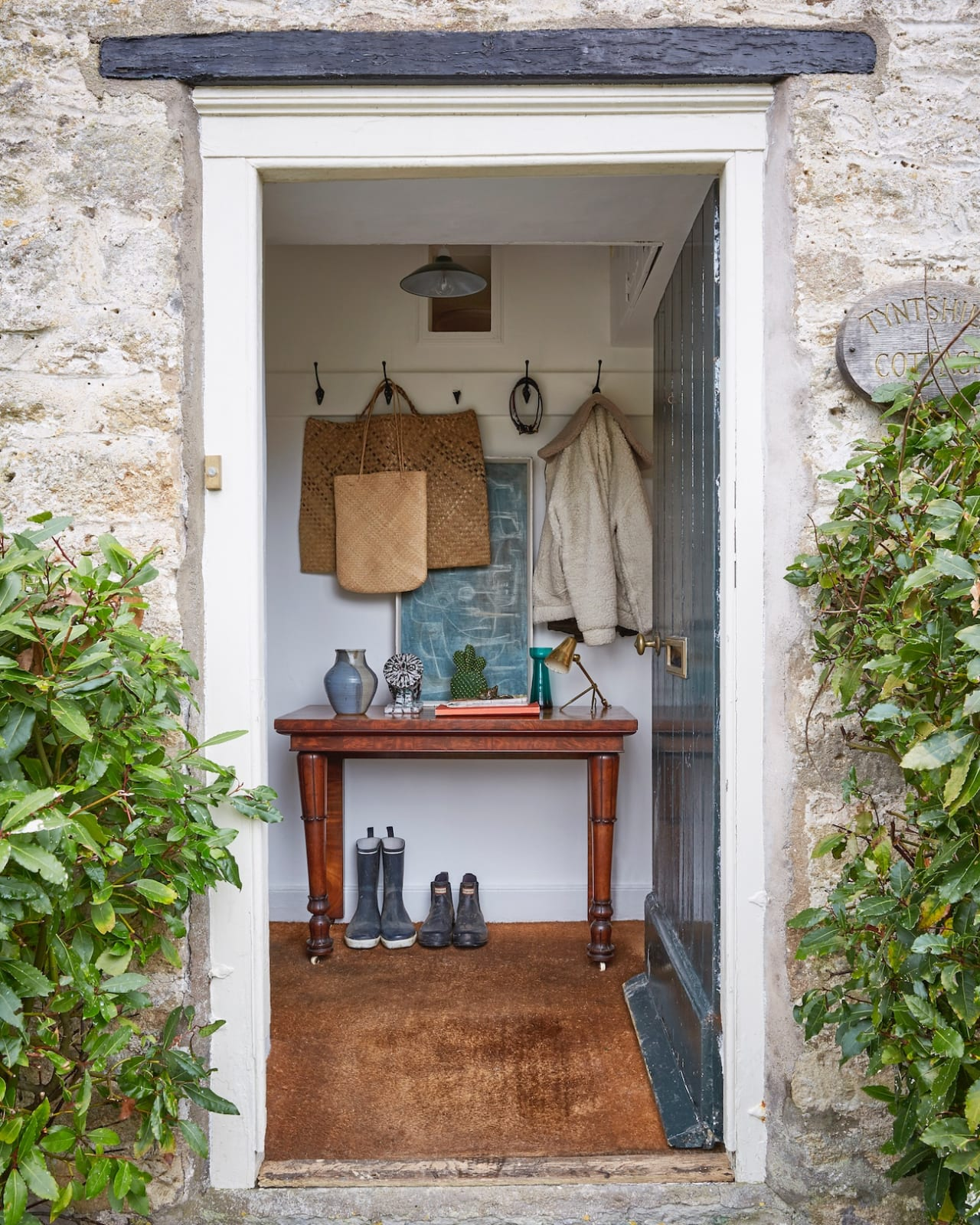 The front door to the cottage is painted in the estate's trademark green, opening to a hallway with 19th-century mahogany console table with Egyptian-esque leg details.