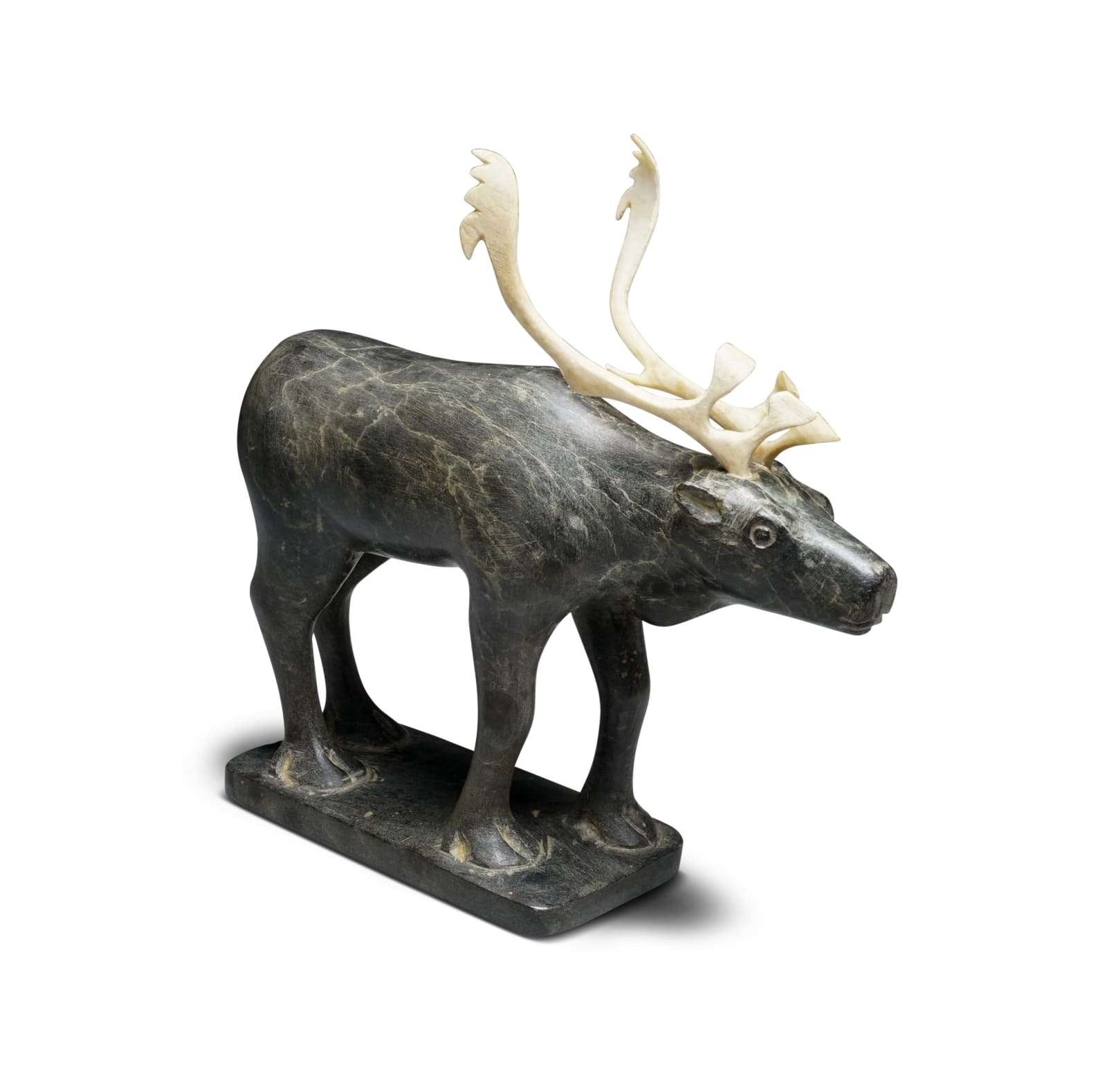 JOANASI KAYAKJUAK (1917-1994) SANIRAJAK (HALL BEACH) Standing Caribou, early 1960s stone and ivory, 5 1/2 x 8 x 2 1/2 in (14 x 20.3 x 6.3 cm) ESTIMATE: $600 — $900 New Price: $550