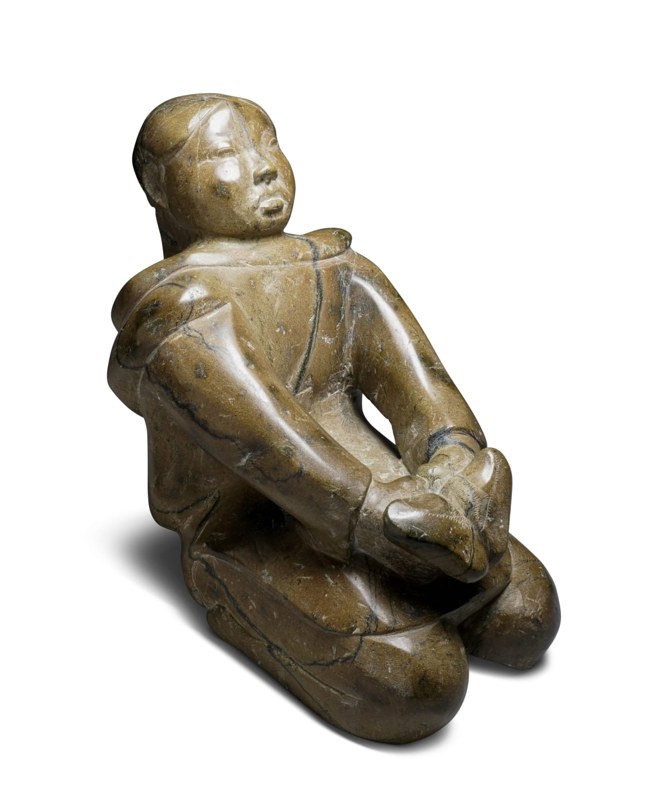 LOT 3 OSUITOK IPEELEE, R.C.A. (1923-2005) KINNGAIT (CAPE DORSET) Woman Holding Kamiks, early-mid 1970s stone, 12 x 7 1/2 x 11 in (30.5 x 19.1 x 27.9 cm) ESTIMATE: $3,500 — $4,500