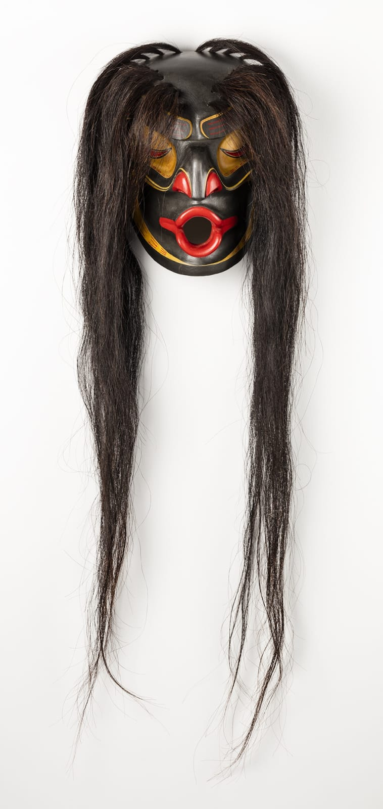 Lot 117 KLATLE-BHI (1966-), SQUAMISH / KWAKWAKA'WAKW Dzoonakwa, 1996 polychrome wood, hair, fabric strap, 13 x 8.75 x 6.5 in (33 x 22.2 x 16.5 cm) excluding hair Estimate: $4,000⁠⁠⁠— $6,000