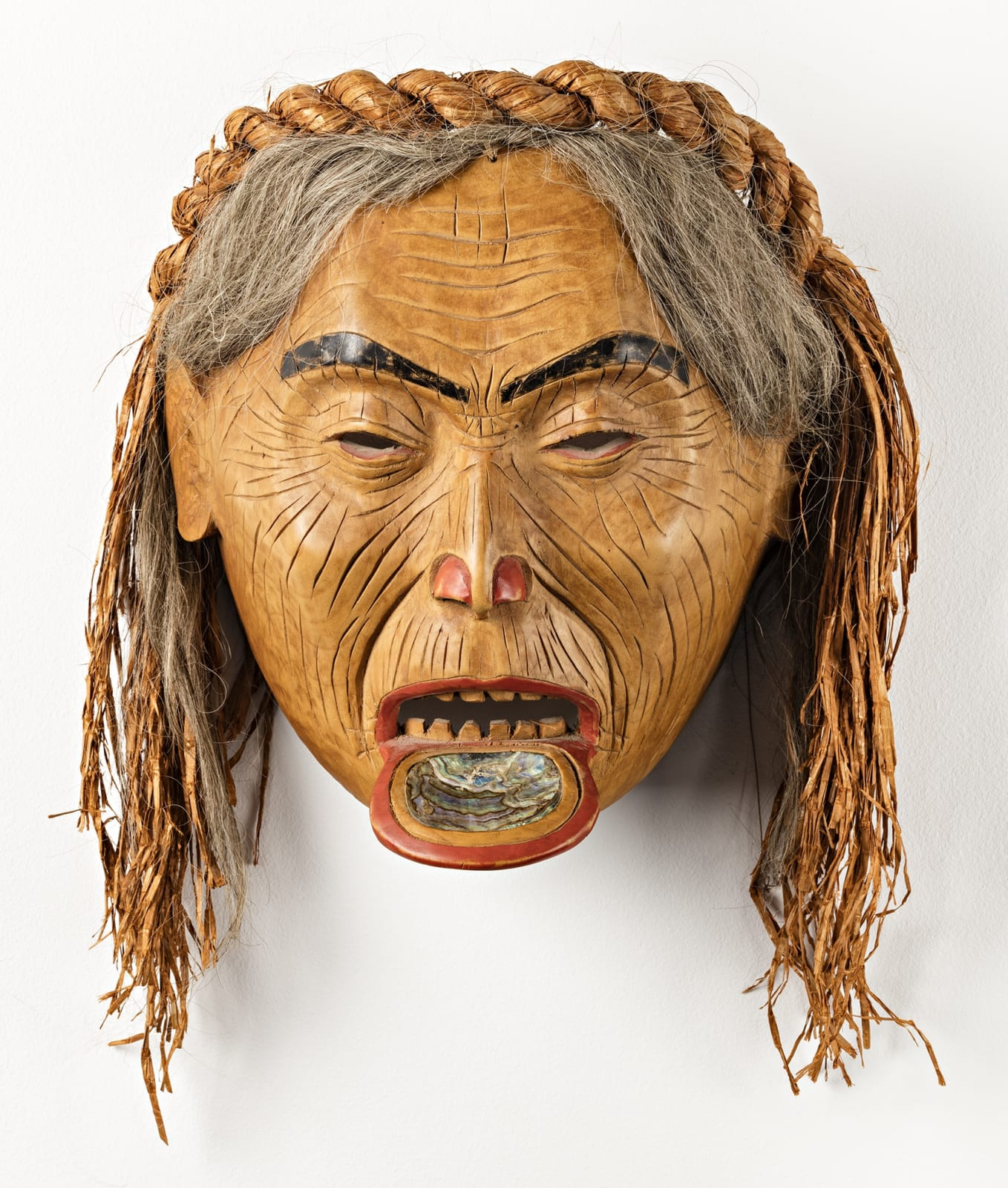 Lot 67 FREDA DIESING (1925-2002), HAIDA, PRINCE RUPERT Old Woman with Labret, 1973 alder, cedar bark, hair, abalone, and paint, 8 x 9 x 6 in (20.3 x 22.9 x 15.2 cm) excluding hair Estimate: $5,000⁠ ⁠⁠— $7,000
